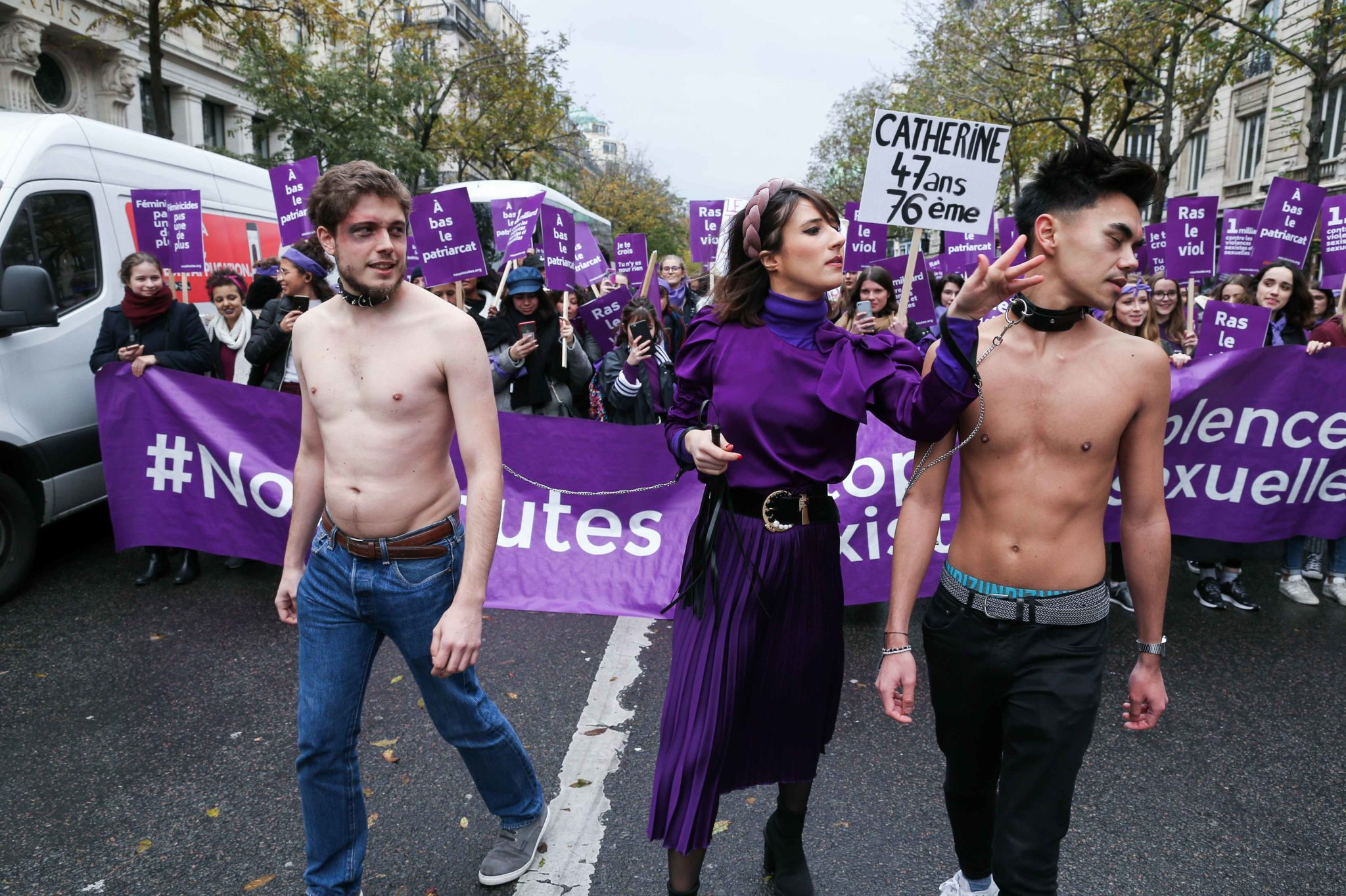 Men in chains are exposed during a protest to condemn violence against women, on November 23, 2019, in Paris. Wearing purple – the adopted colour of feminist struggles – activists are taking to the streets of Paris and other French cities to speak out