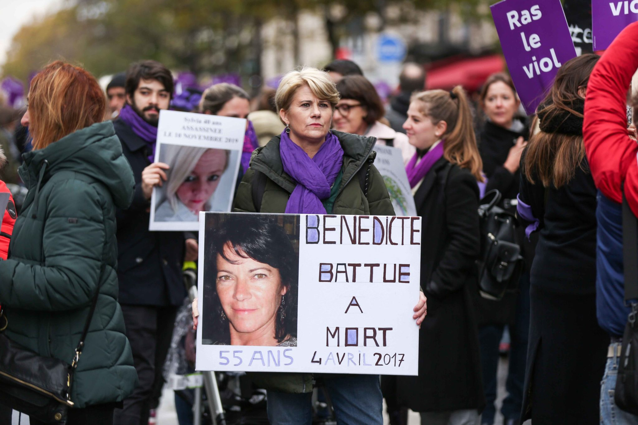 A family member holds the portrait of a woman killed, during a protest to condemn violence against women, on November 23, 2019, in Paris, in front of the Garnier Opera House. Wearing purple – the adopted colour of feminist struggles – activists are ta
