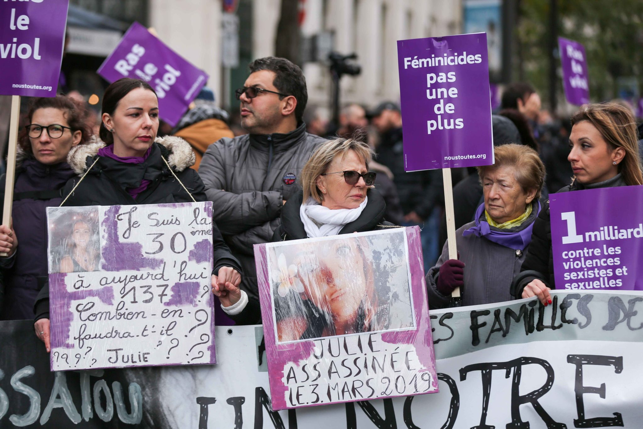 Family members hold the portrait of women killed, during a protest to condemn violence against women, on November 23, 2019, in Paris, in front of the Garnier Opera House. Wearing purple – the adopted colour of feminist struggles – activists are taking