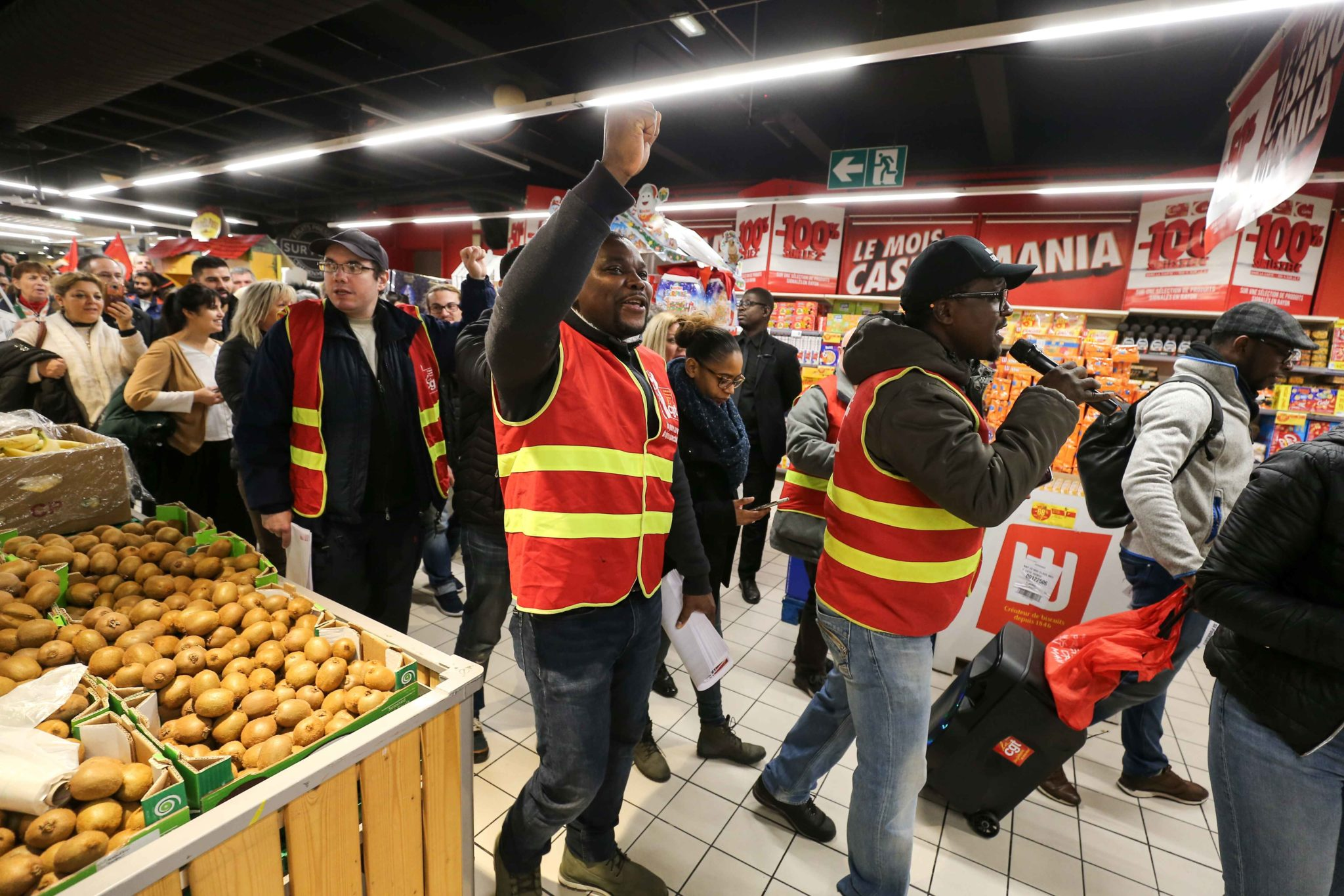 French General Confederation of Labour (CGT) union members walk inside Casino supermarket in the 13th arrondissement of Paris on November 26, 2019, during a demonstration against the deterioration in working conditions and the take over by the German group