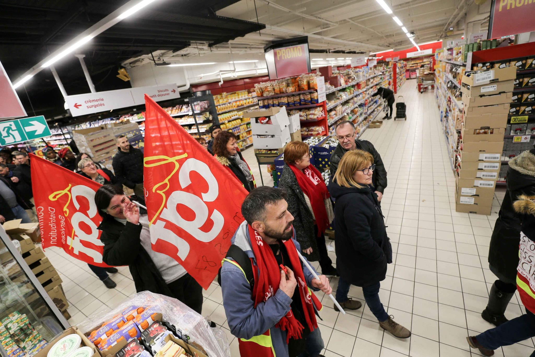 French General Confederation of Labour (CGT) union members holding flags walk inside Casino supermarket in the 13th arrondissement of Paris on November 26, 2019, during a demonstration against the deterioration in working conditions and the take over by th