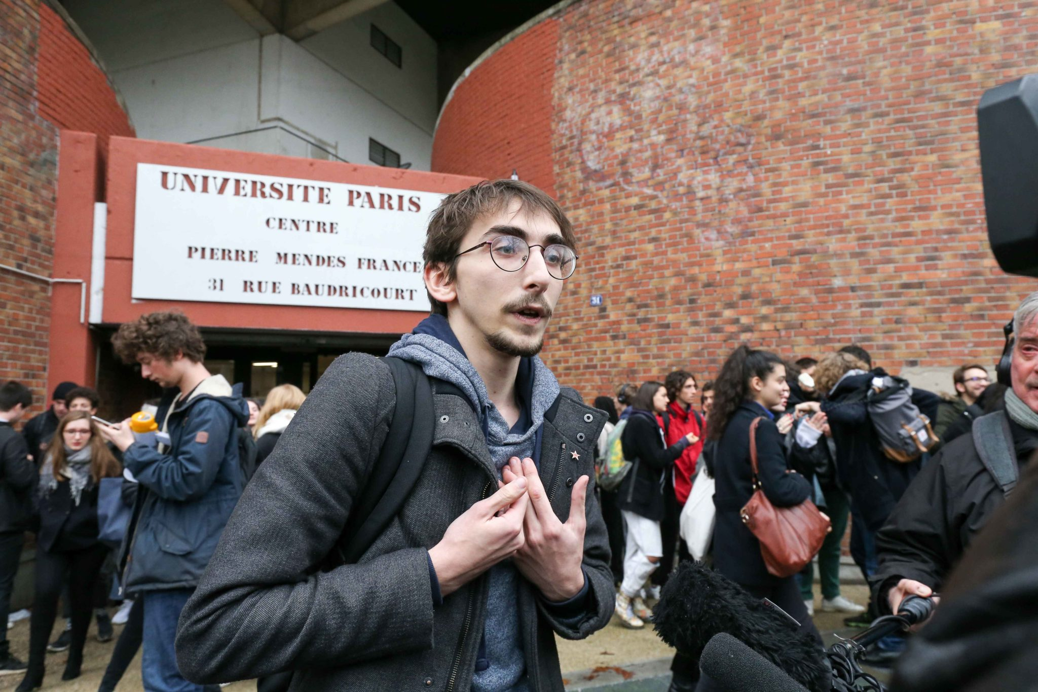 A spokesperson of students speaks with the press in front of the University of Paris-1 Tolbiac, on November 26, 2019, as French students demonstrate against their precariousness after the suicide attempt of a 22-year-old student by immolation on November 8