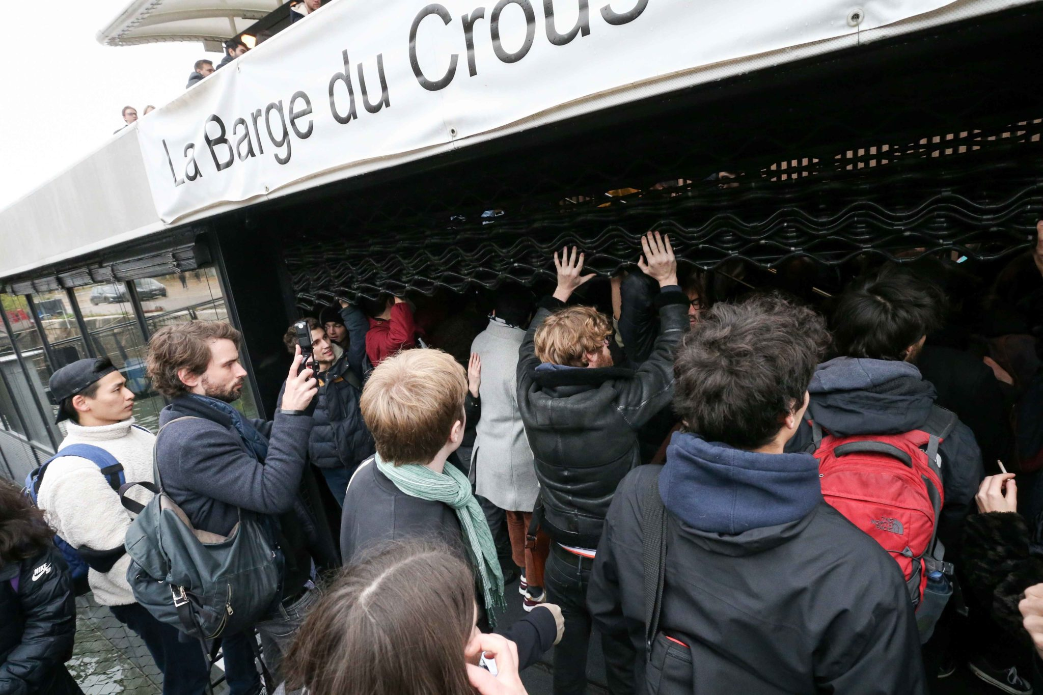French students try to break down the entrance of the Crous (Regional Center of University and Academic Services) restaurant boat on the Seine in Paris as they demonstrate against their precariousness on November 26, 2019, after the suicide attempt of a 22