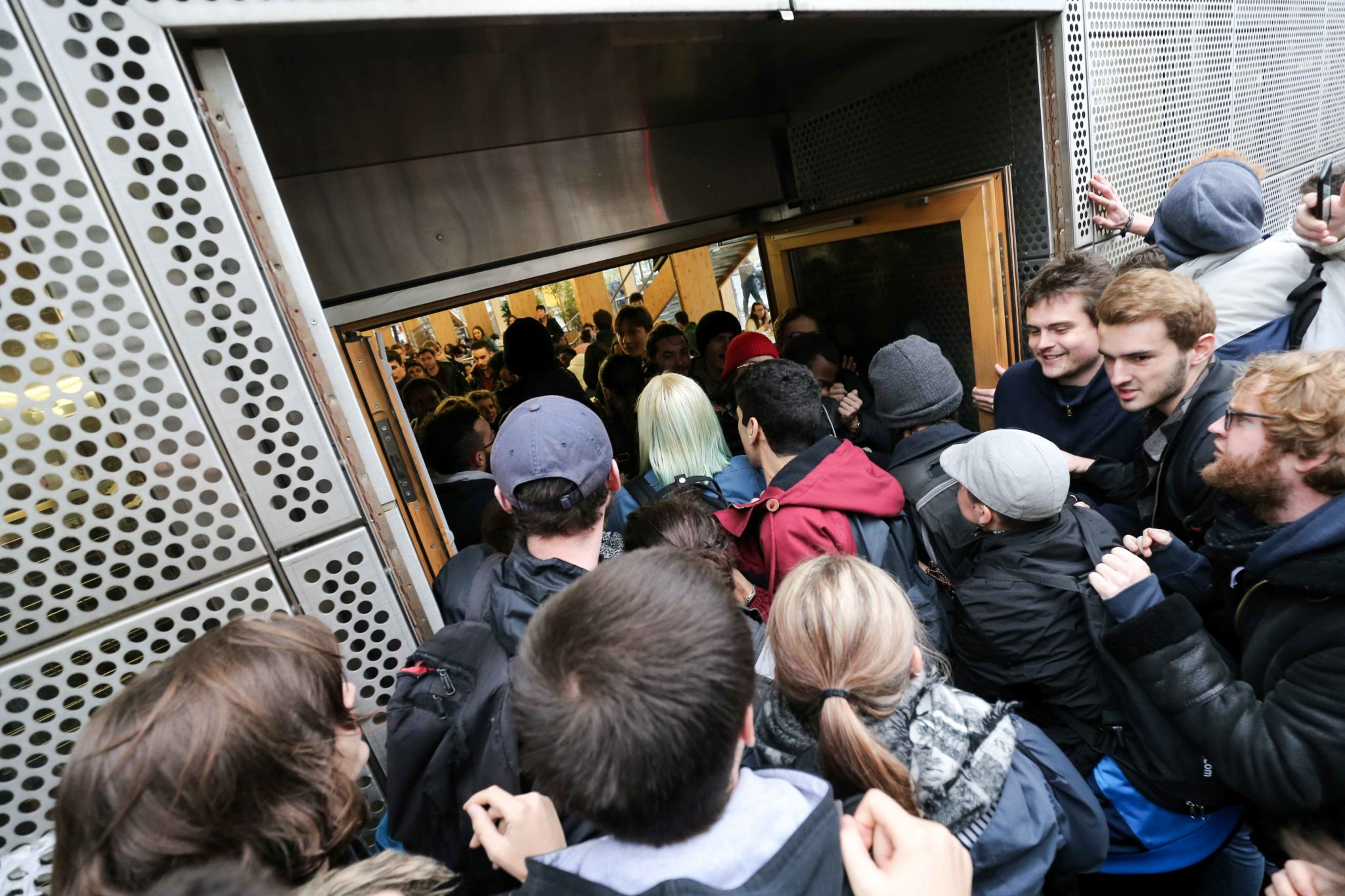 French students try to break down the entrance of the University restaurant near the University Paris Diderot as they demonstrate against their precariousness in Paris, on November 26, 2019, after the suicide attempt of a 22-year-old student by immolation