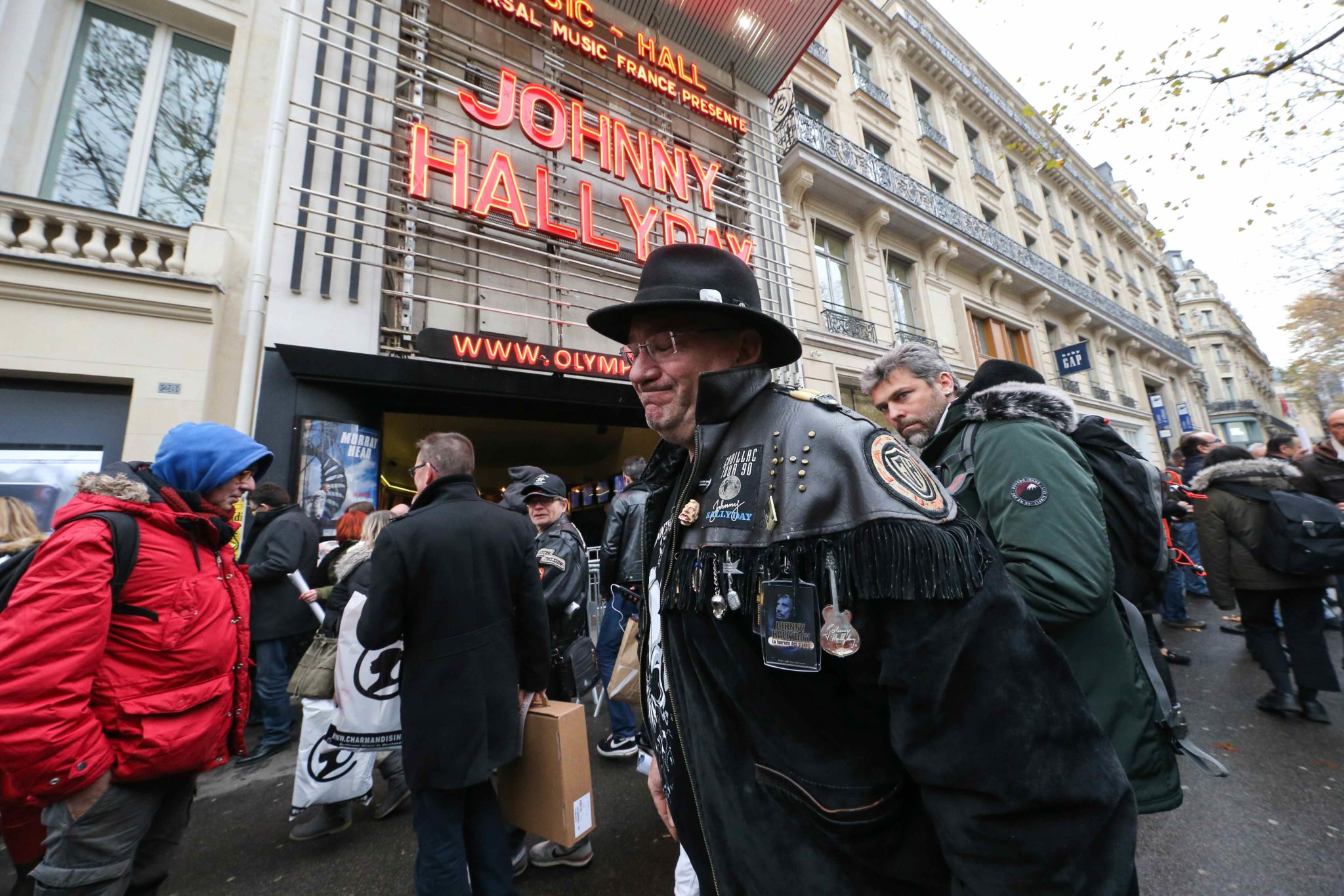 A fan of the French singer Johnny Hallyday poses in front of the  Olympia Hall in Paris where  a tribute was paid to this legend of French music on Sunday, December 1, 2019, almost two years after his death. For the occasion, the letters of his name shone