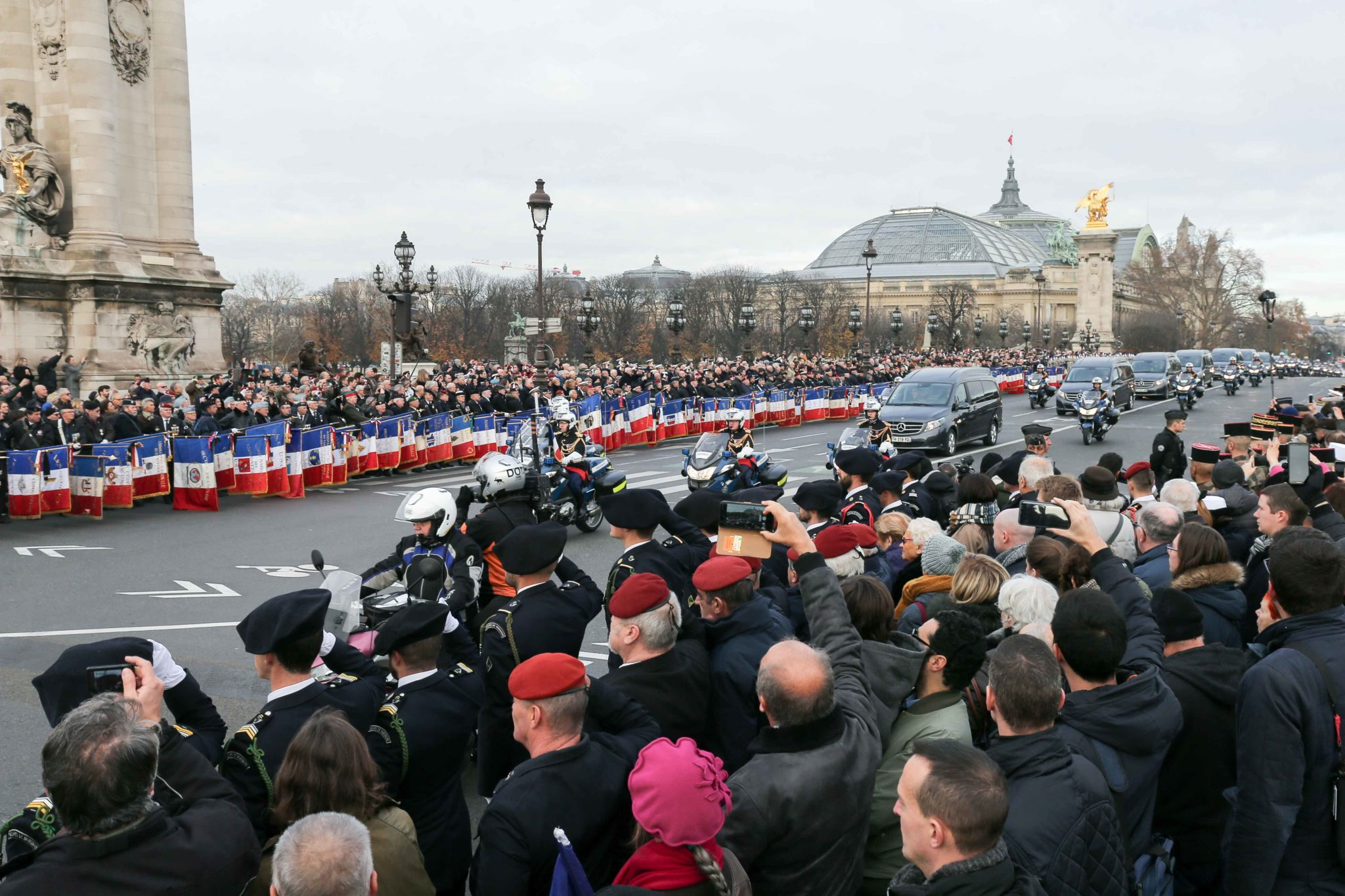 Soldiers and flag bearers salute as the funeral convoy passes on Alexandre III Bridge in front of the Invalides monument in Paris on December 2, 2019, ahead of a ceremony to pay tribute to 13 French soldiers who died in a helicopter collision in Mali on No