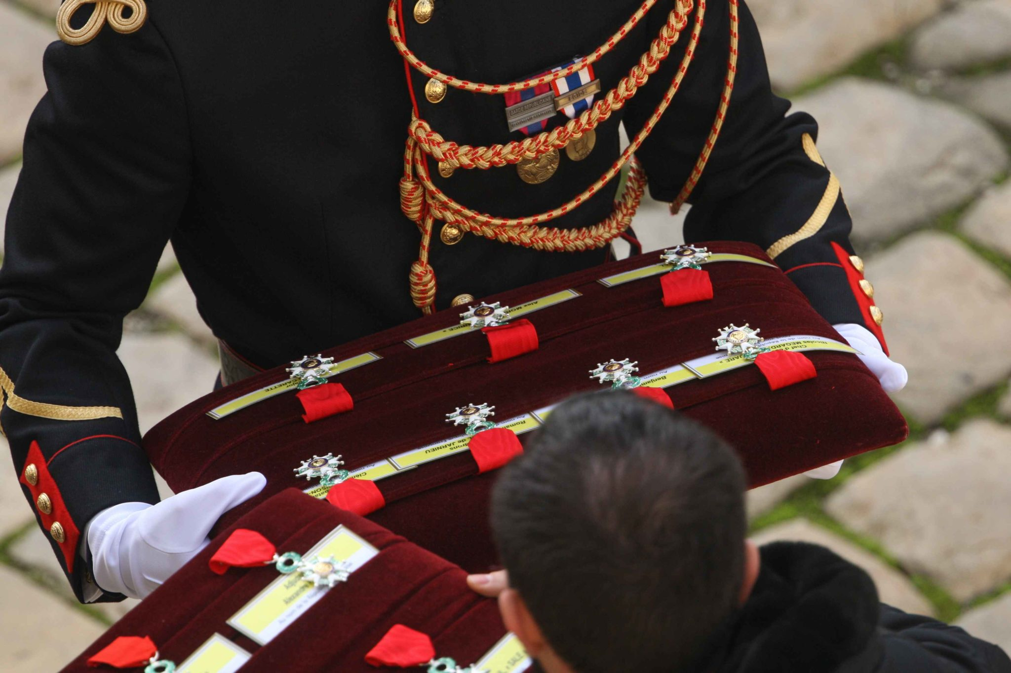 Soldier holds a cushion with Legion of Honor medals to posthumously awards a soldier during a tribute ceremony on December 2, 2019 at the Invalides monument, in Paris, for the 13 French soldiers killed in Mali. In its biggest military funeral in decades, F