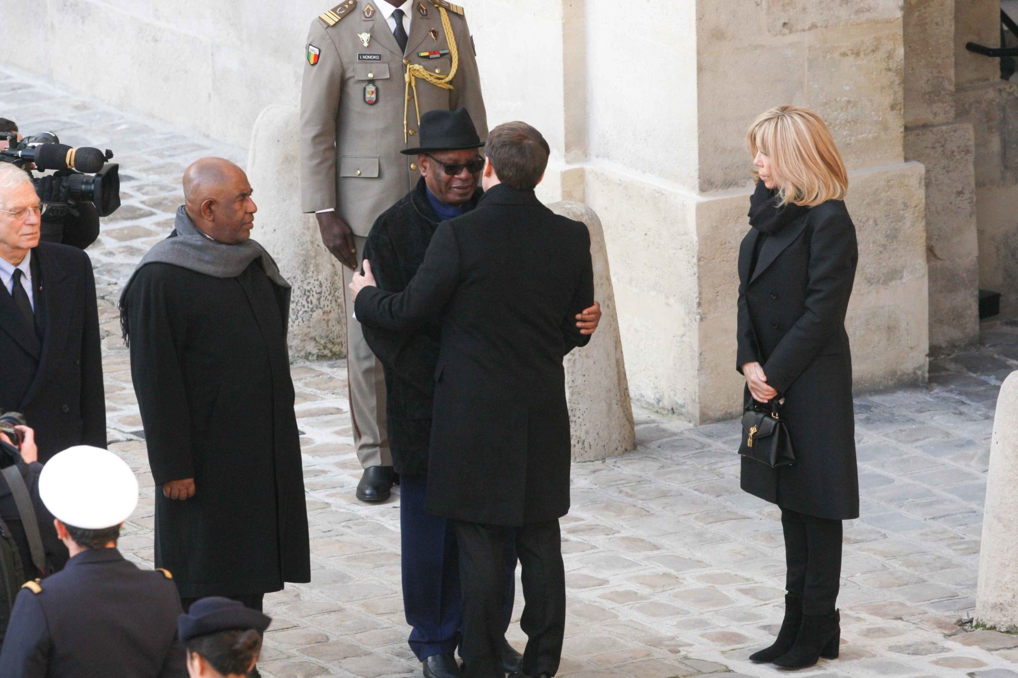 French President Emmanuel Macron (2R) hugs Mali's President Ibrahim Boubacar Keita (3R) while Brigitte Macron looks on prior a ceremony at the Invalides monument in Paris on December 2, 2019, to pay tribute to 13 French soldiers who died in a helicopter co