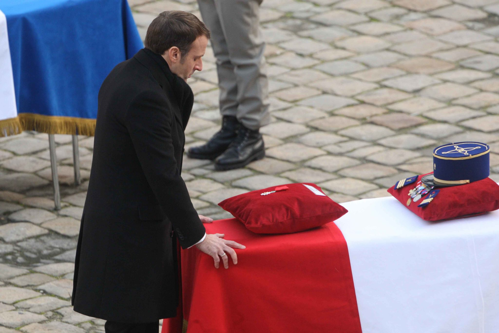 French President Emmanuel Macron touches the coffin after posthumously awarding a soldier with the Legion of Honor during a tribute ceremony on December 2, 2019 at the Invalides monument, in Paris, for the 13 French soldiers killed in Mali. In its biggest