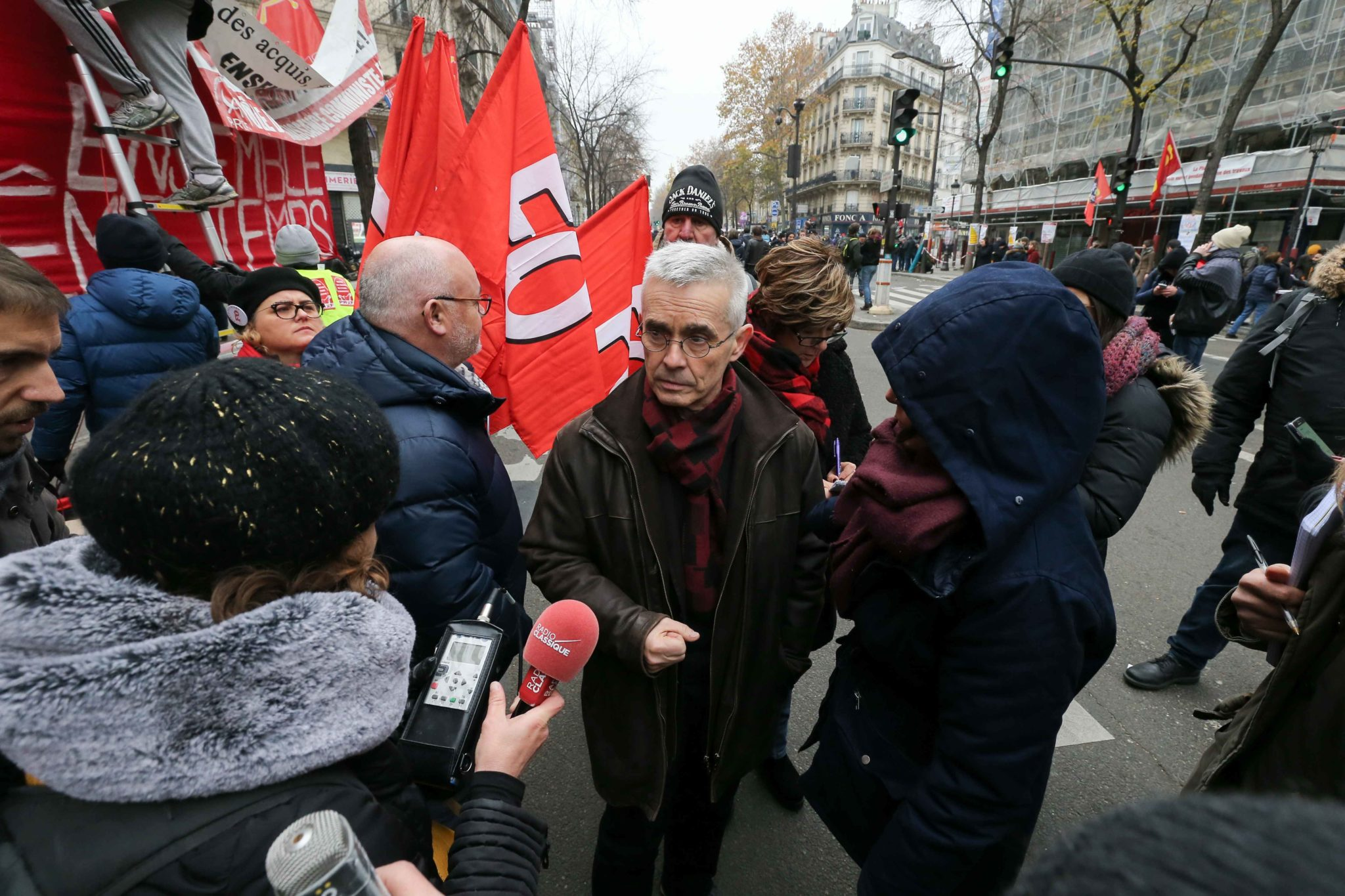 Secretary-General of the French Union Force Ouvriere (FO) Yves Veyrier (C) talks with the press during a demontration to protest against the pension overhauls, in Paris, on December 5, 2019 as part of a national general strike. Trains cancelled, schools cl