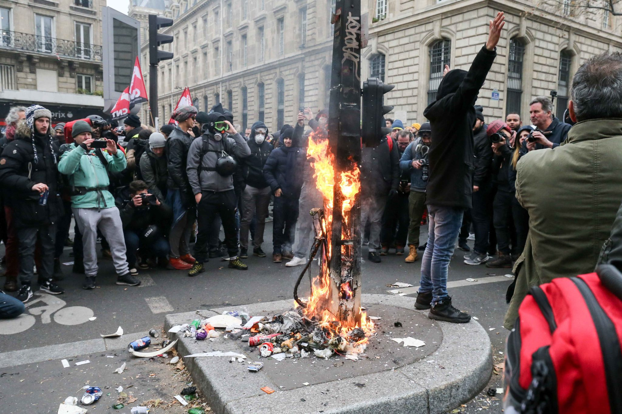 Protesters burn a traffic sign post during a demontration to protest against the pension overhauls, in Paris, on December 5, 2019 as part of a national general strike. Trains cancelled, schools closed: France scrambled to make contingency plans on for a hu