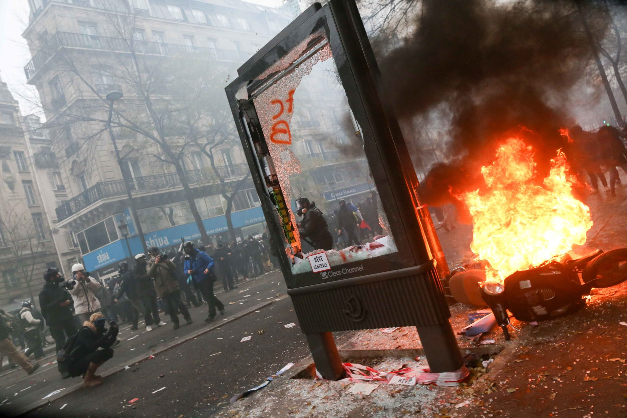 A publicity pane is destroyed and a scooter set on fire during a demontration to protest against the pension overhauls, in Paris, on December 5, 2019 as part of a national general strike. Trains cancelled, schools closed: France scrambled to make contingen