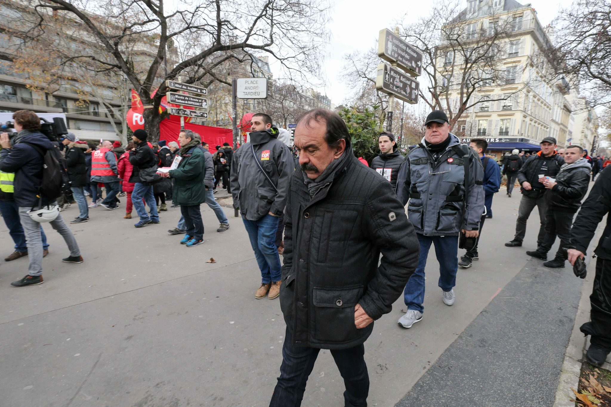 CGT union leader Philippe Martinez (C) arrives at a demonstration on December 10, 2019 in Paris as part of the sixth day of a strike of public transport operators SNCF and RATP employees over French government's plan to overhaul the country's retirement sy