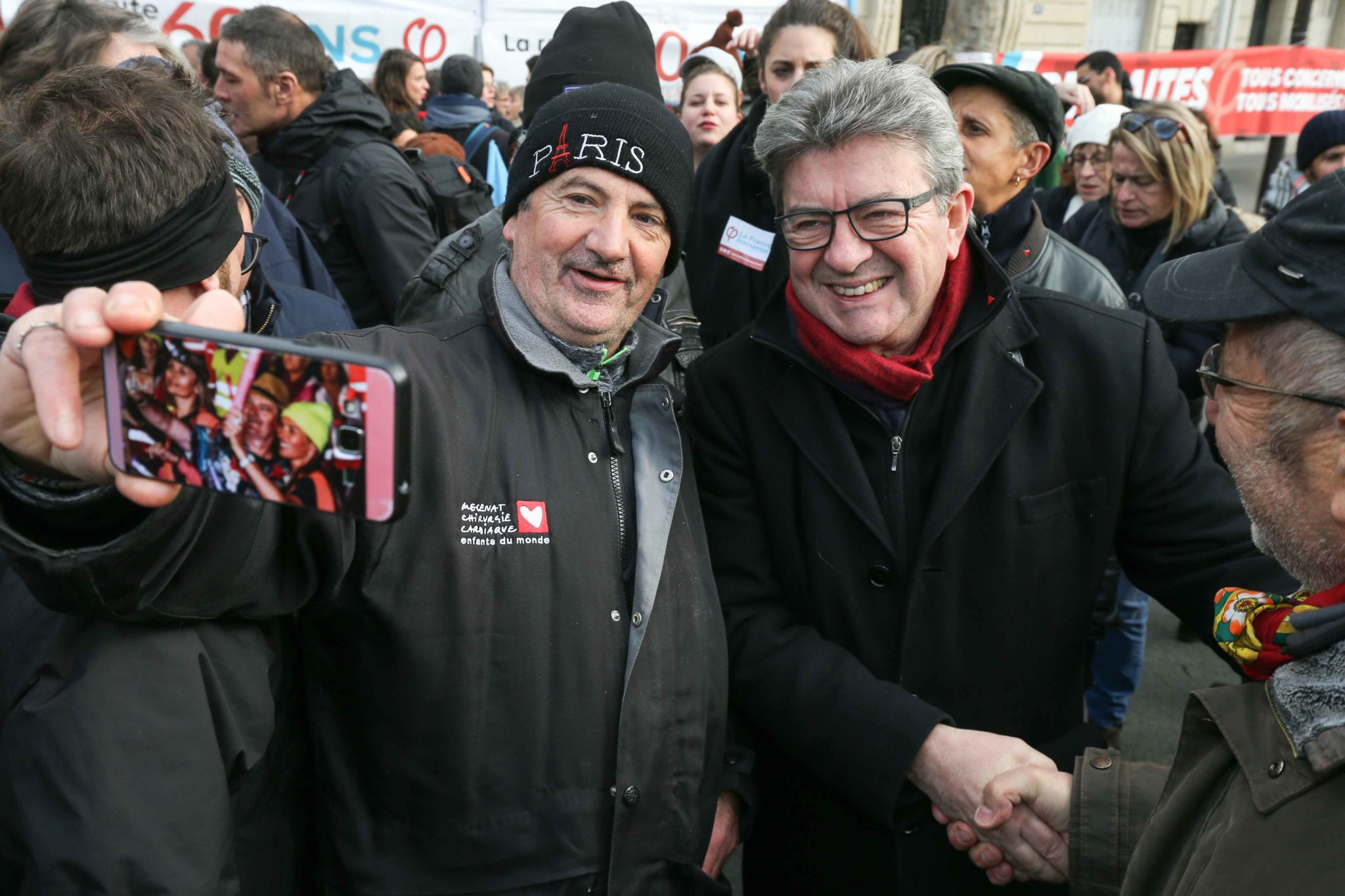 France's leftist party La France Insoumise (LFI) president Jean-Luc Melenchon (R) talks with demonstrators during a march in Paris on December 10, 2019 on a sixth day of a strike of public transport operators SNCF and RATP employees over French government'