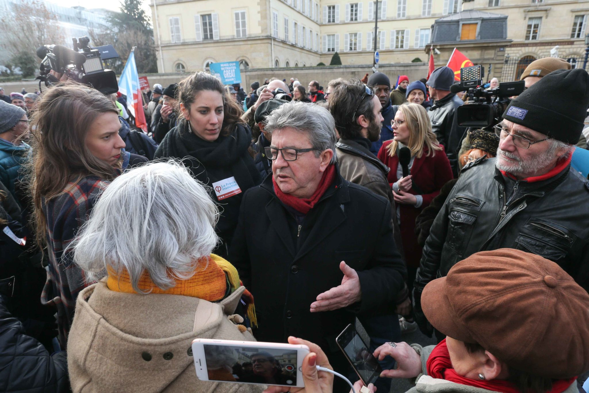 France's leftist party La France Insoumise (LFI) president Jean-Luc Melenchon (C) talks with demonstrators during a march in Paris on December 10, 2019 on a sixth day of a strike of public transport operators SNCF and RATP employees over French government'