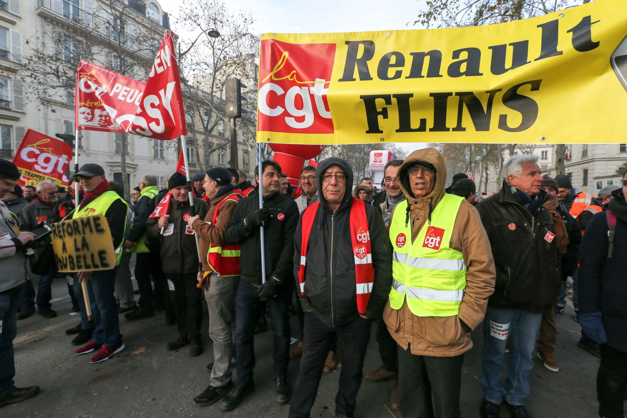 Workers of the French manufacturer Renault takes part in a demonstration on December 10, 2019 in Paris as part of the sixth day of a strike of public transport operators SNCF and RATP employees over French government's plan to overhaul the country's retire
