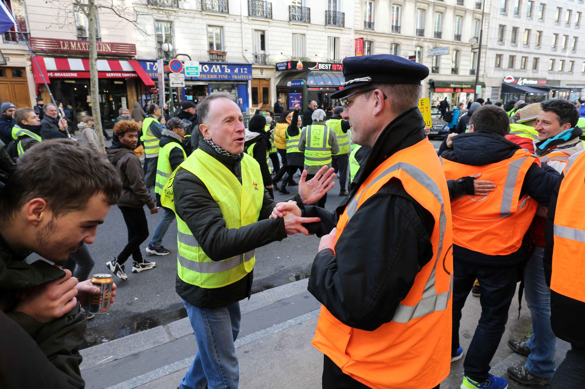 Striking railway workers wearing an orange vest of Paris' RATP public transport operator fraternises with yellow vests during a demonstration called by French national trade union General Confederation of Labour (CGT) against the pension reform on January