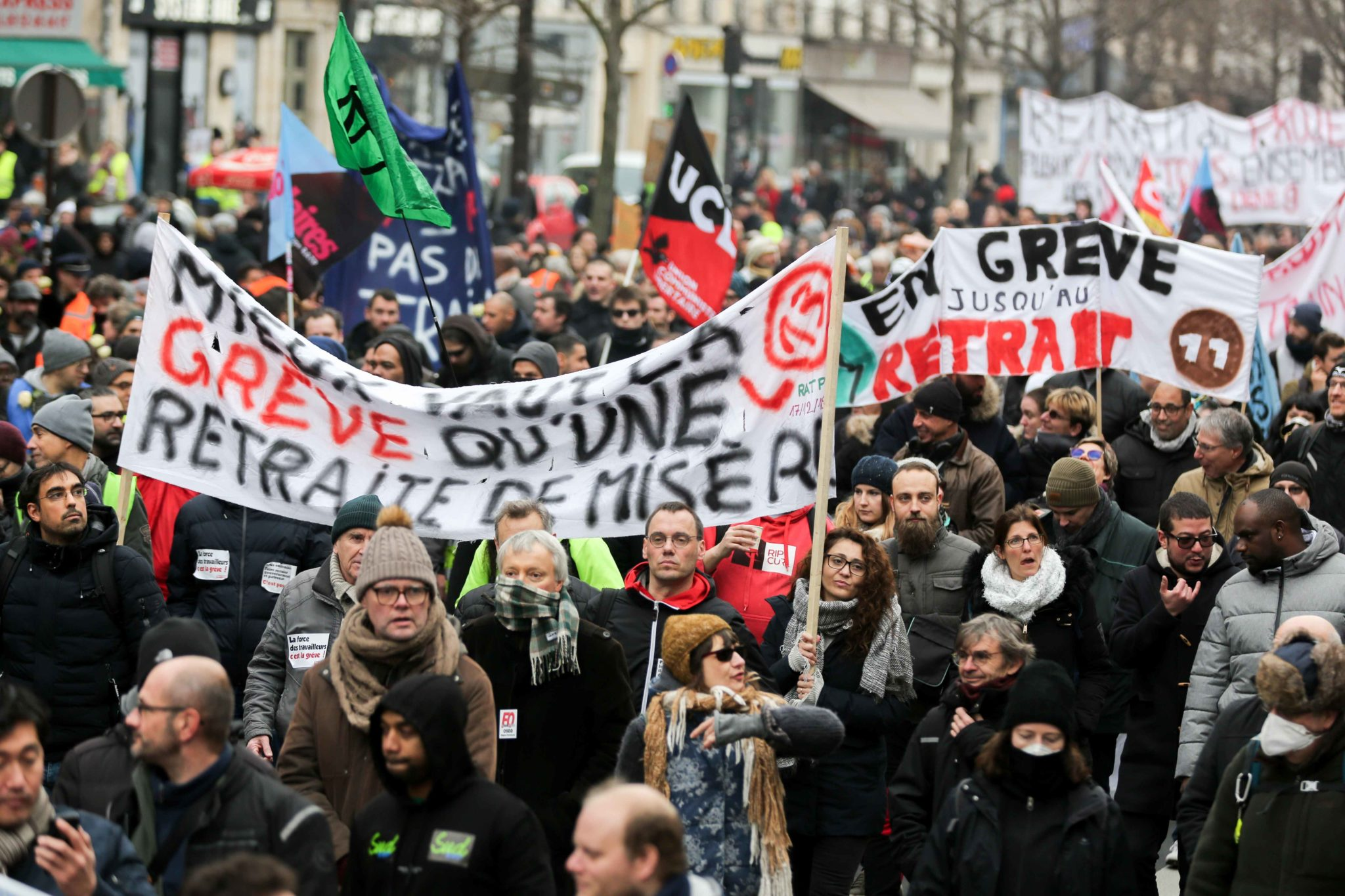 "Protestors hold a banner reading ""Strike is better than a meagre pension"" during a demonstration called by French national trade union General Confederation of Labour (CGT) against the pension reform on January 4, 2020, on the Place de la Republique in Par"