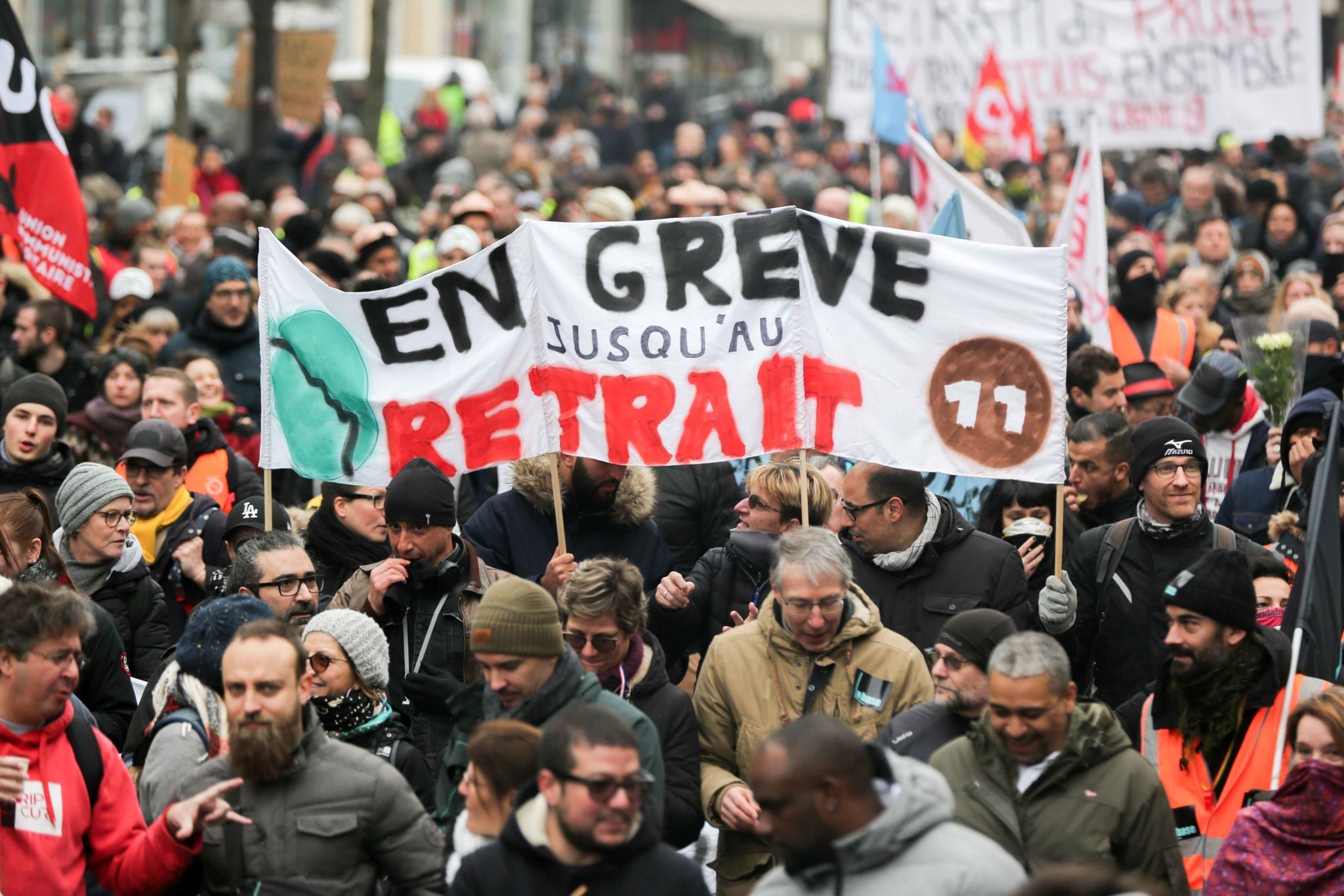 "People hold a banner reading ""On strike untill withdrawal"" during a demonstration called by French national trade union General Confederation of Labour (CGT) against the pension reform on January 4, 2020, in Paris. After 30 days of strike, unions opposed t"