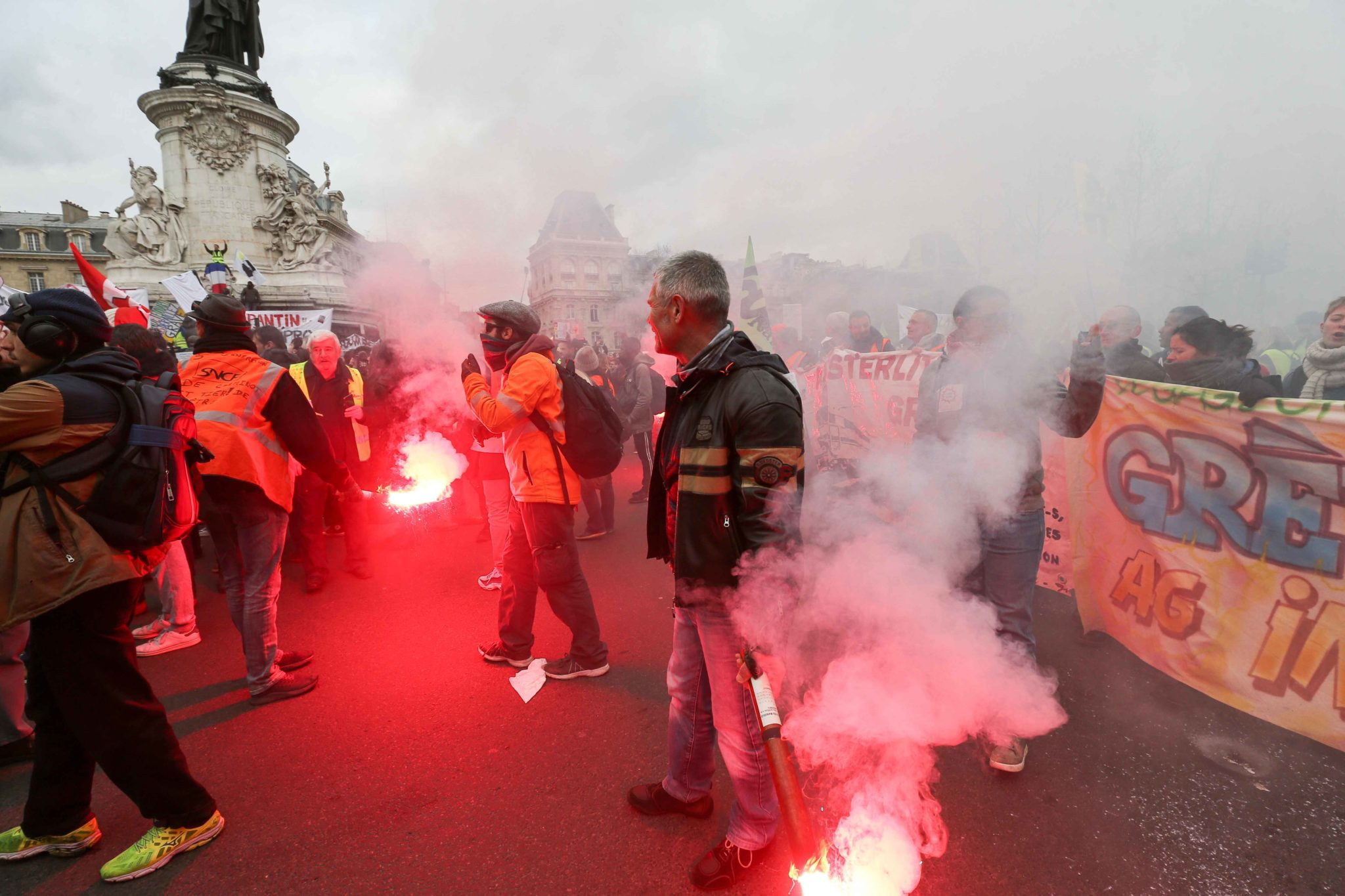Striking railway workers holds red flares during a demonstration called by French national trade union General Confederation of Labour (CGT) against the pension reform on January 4, 2020, on the Place de la Republique in Paris, on January 4, 2020. After 30