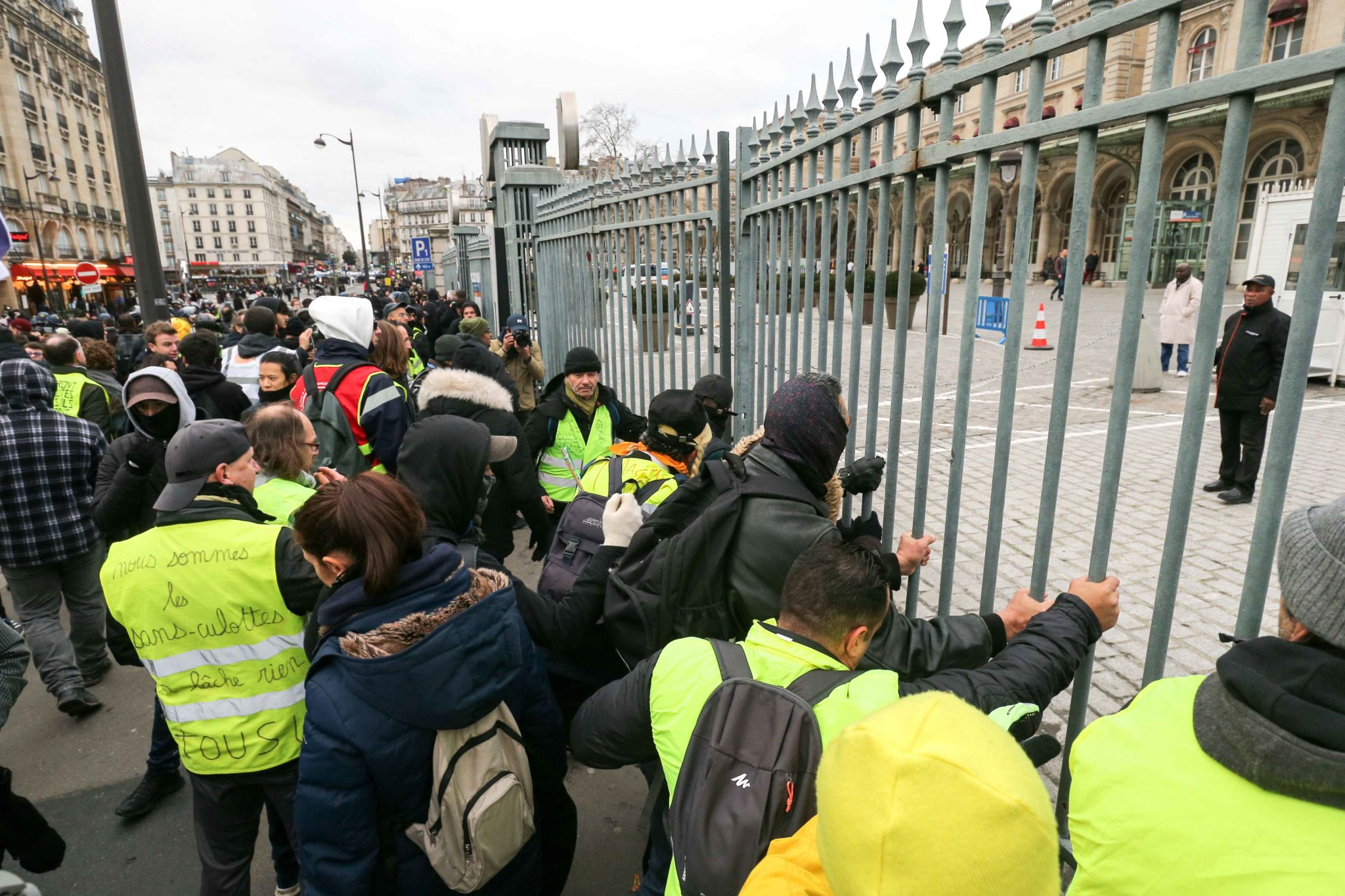 Demonstrators wearing yellow vests break down the gate of the Gare de l'Est train station in Paris during a demonstration called by French national trade union General Confederation of Labour (CGT) against the pension reform on January 4, 2020. After 30