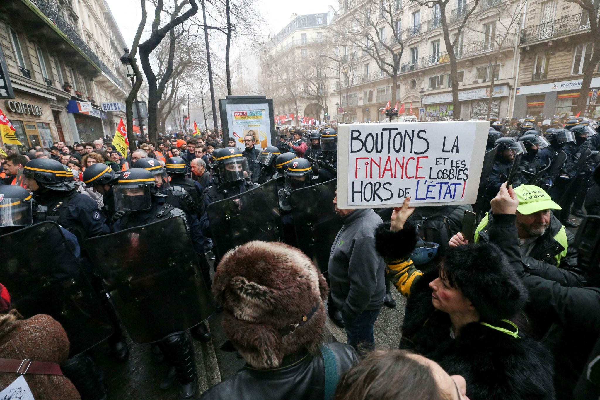 A woman holds a placard reading «Let's throw the finance and lobbies out of the State » in front of CRS riot policemen during a demonstration in Paris, on January 9, 2020, on the 36th day of a nationwide multi-sector strike against French government's