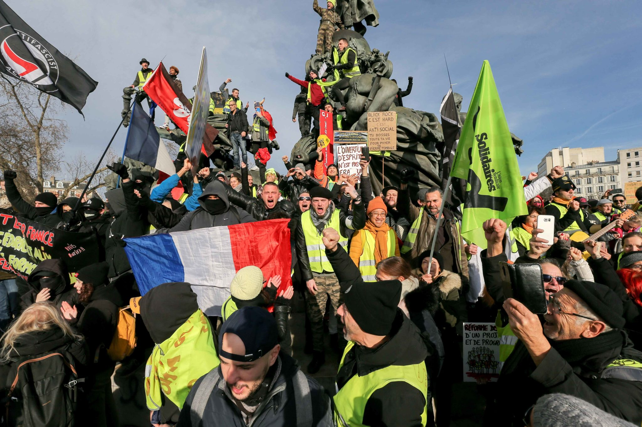 Yellow vests climb the statue of the Nation Square (Place de la Nation) during a demonstration in Paris, on January 11, 2020, as part of a nationwide multi-sector strike against the French government's pensions overhaul. The country has been hit by 37 days