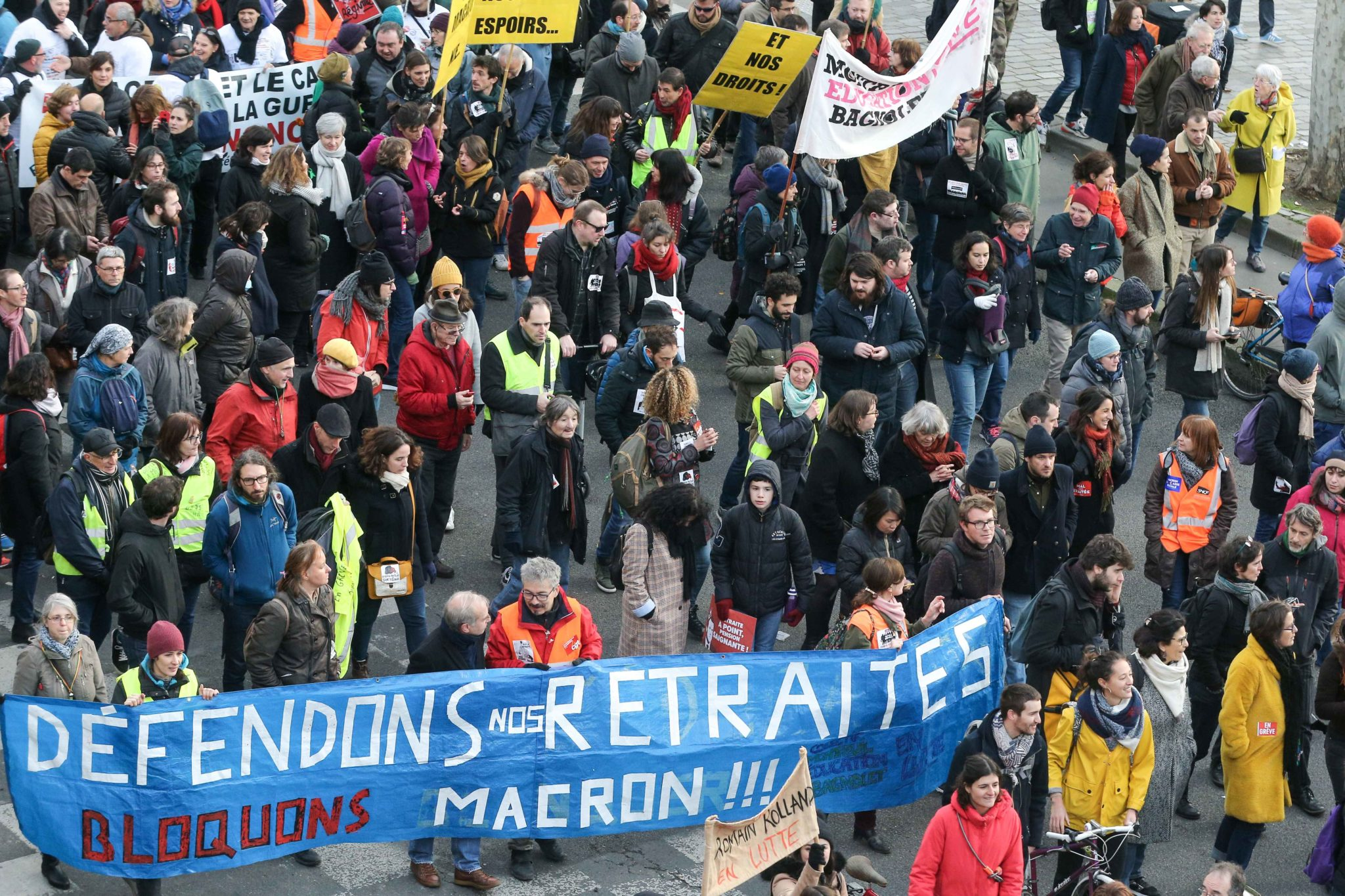 "Protestors walk behind a banner reading "" Defend our pensions, block Macron"" during a demonstration in Paris, on January 11, 2020, as part of a nationwide multi-sector strike against the French government's pensions overhaul. The country has been hit by 37"