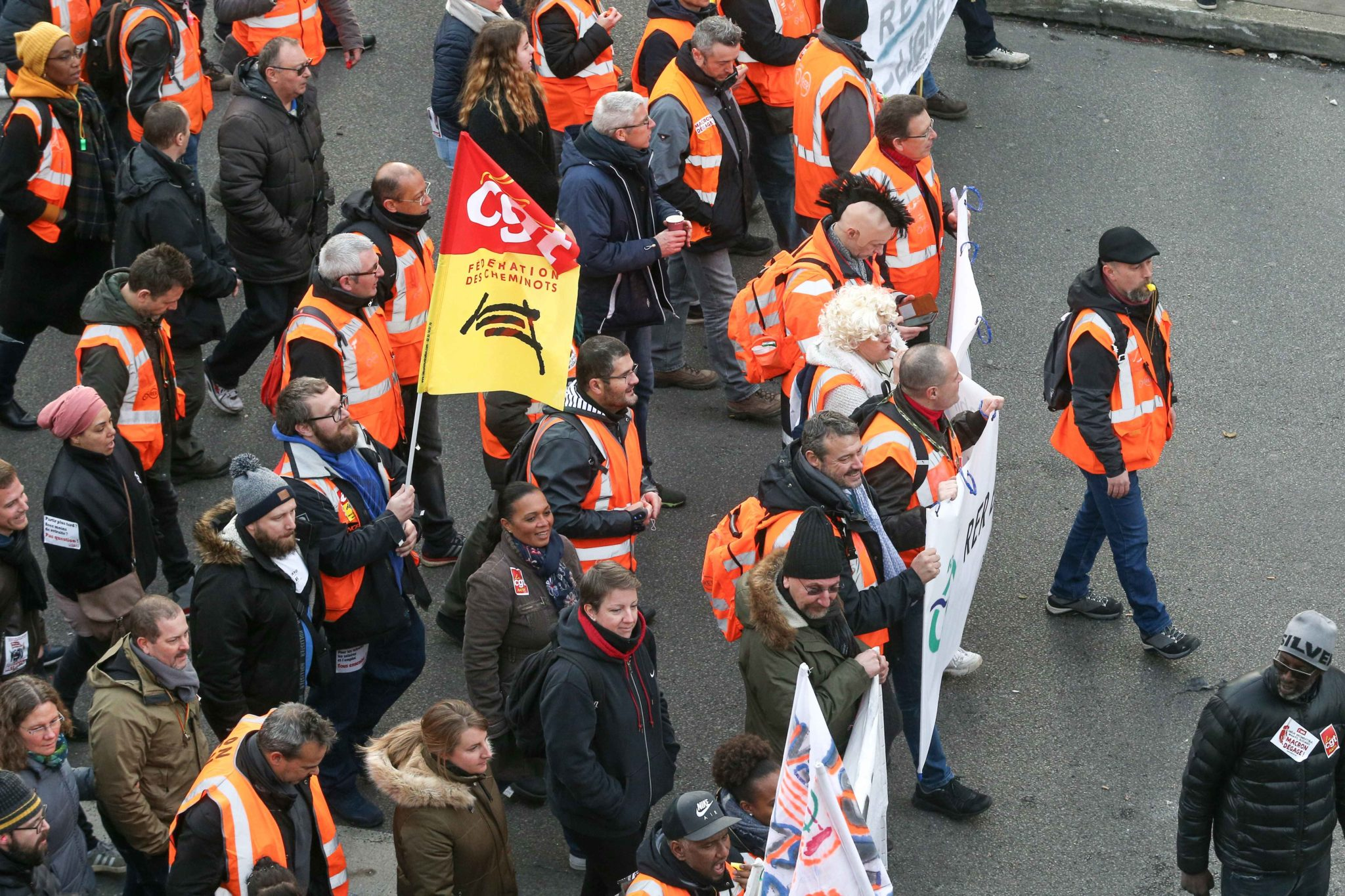 Striking railway workers wearing an orange vest of Paris' RATP and RER public transport operator walk behind a banner during a demonstration in Paris, on January 11, 2020, as part of a nationwide multi-sector strike against the French government's pensions