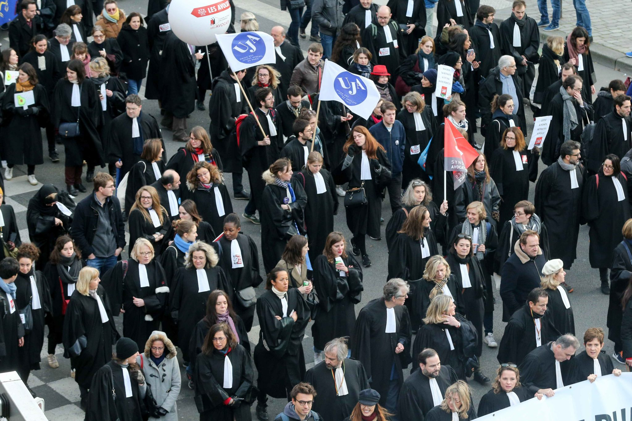 Lawyers wearing their robe walk during a demonstration in Paris, on January 11, 2020, as part of a nationwide multi-sector strike against the French government's pensions overhaul. The country has been hit by 37 days of crippling train and metro stoppages
