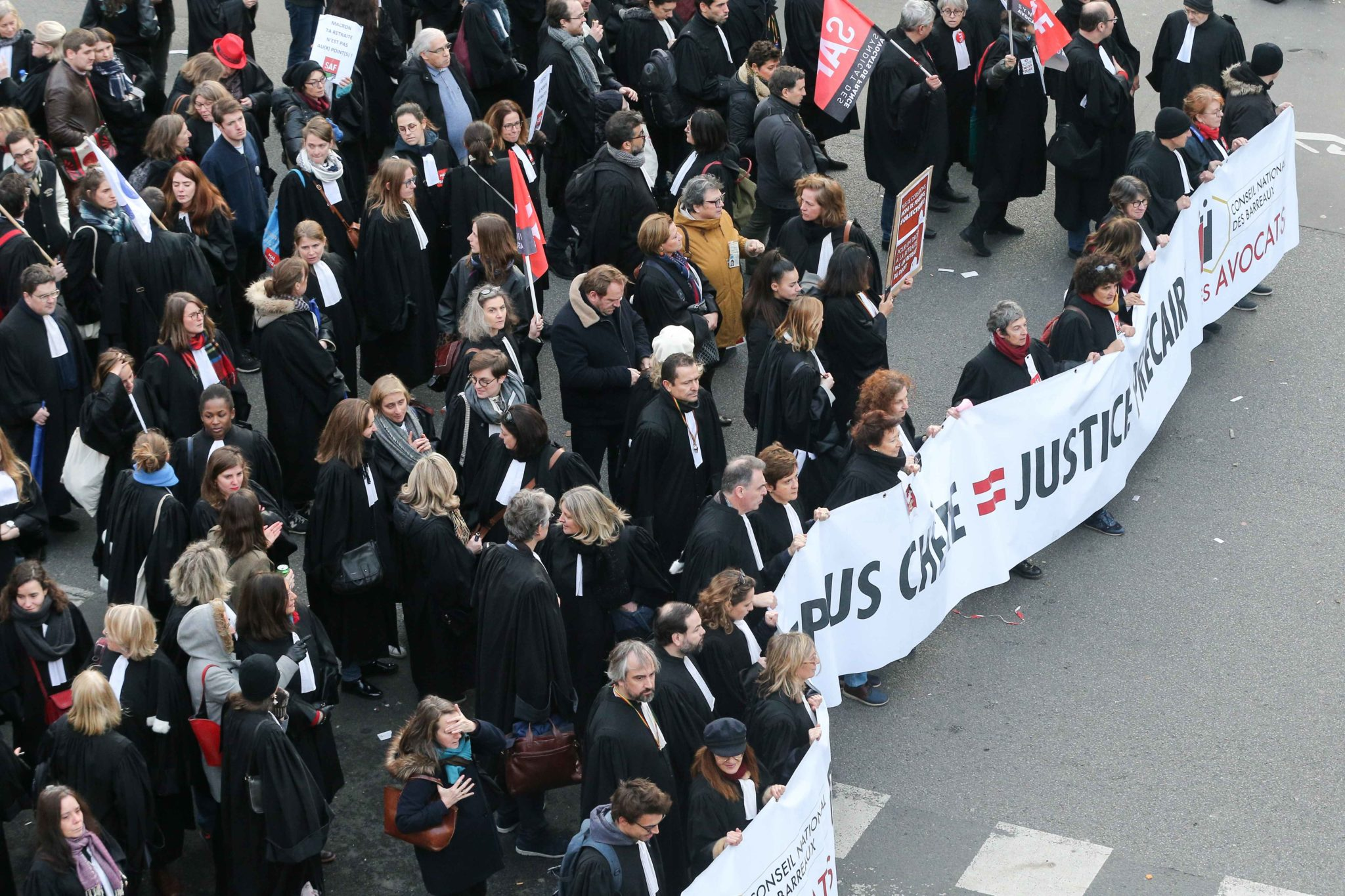 Lawyers wearing their robe walk behind a banner during a demonstration in Paris, on January 11, 2020, as part of a nationwide multi-sector strike against the French government's pensions overhaul. The country has been hit by 37 days of crippling train and