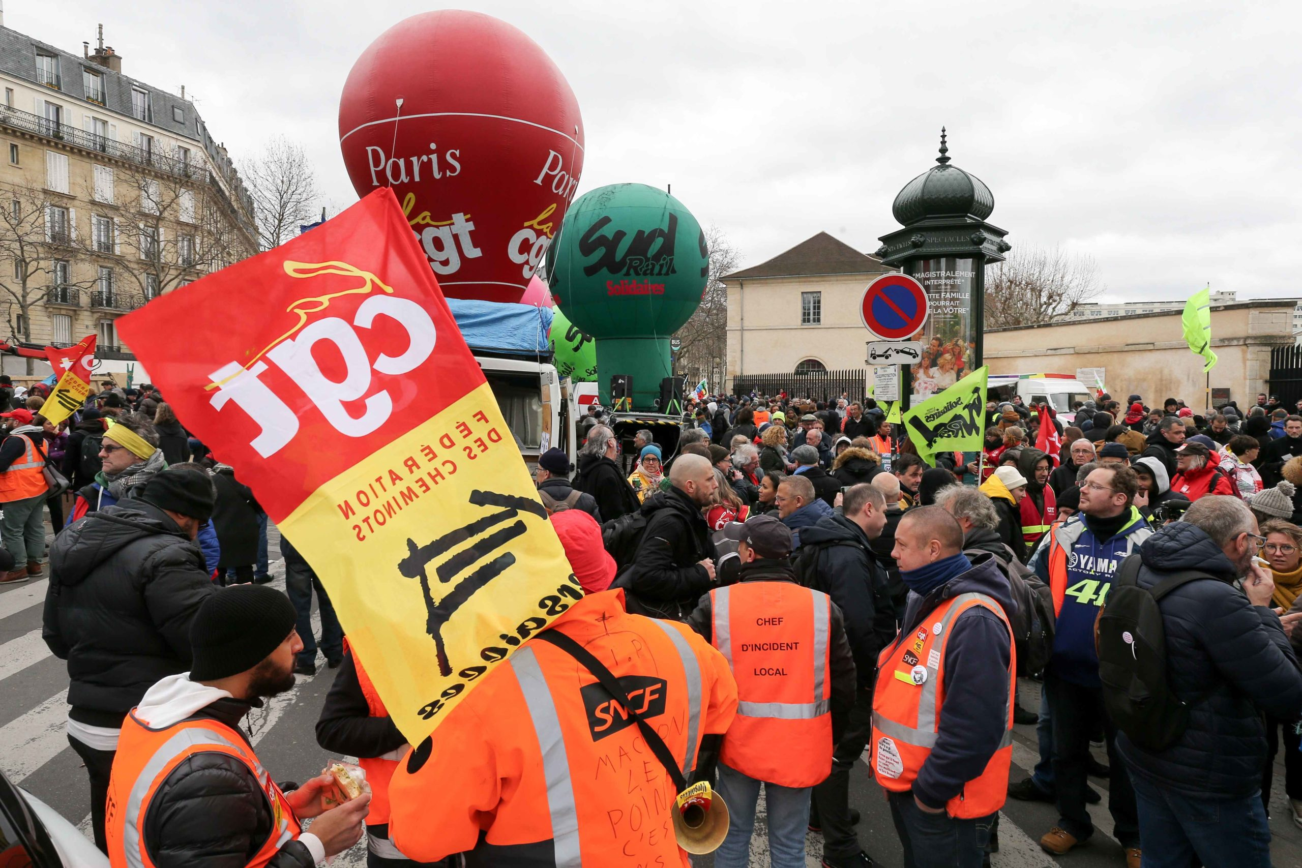 Protesters wearing a public transport operator SNCF high-visibility jacket holds take part in a demonstration in Paris on January 14, 2020, as part of a nationwide multi-sector strike against the French government's pensions overhaul.A transport strike dr