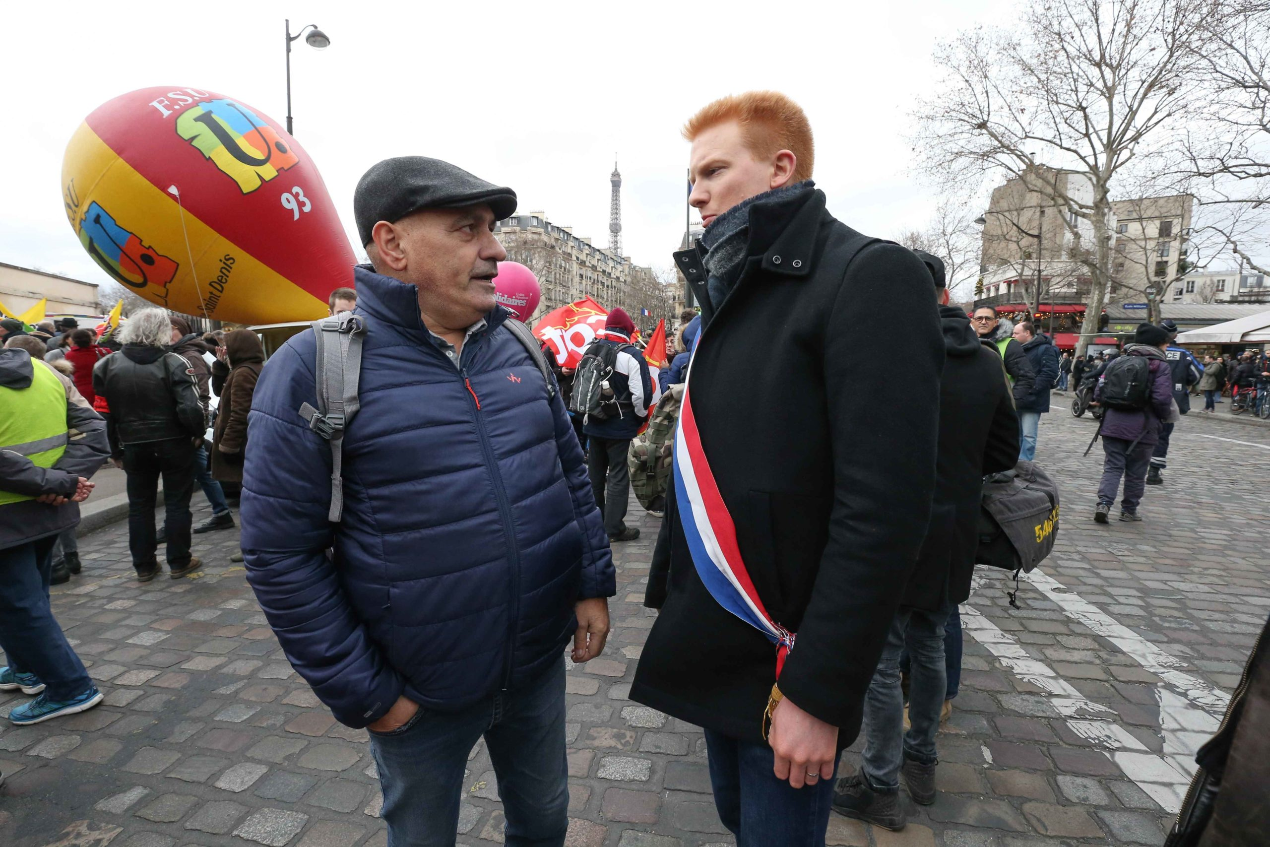 French leftist party La France Insoumise (LFI) MP Adrien Quatennens (R) takes part in a demonstration in front the Tour Eiffel in Paris on January 14, 2020, as part of a nationwide multi-sector strike against the French government's pensions overhaul.A tr