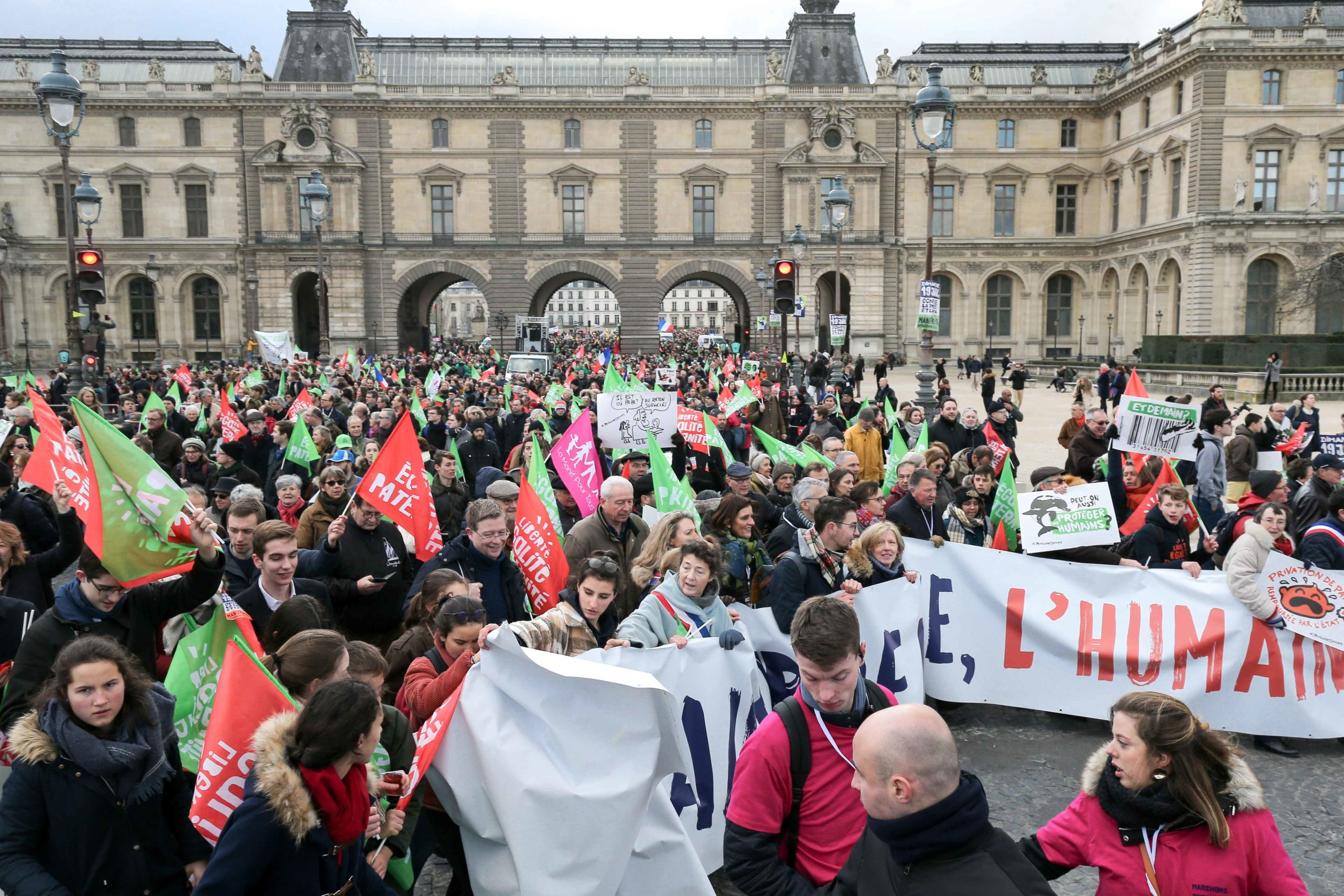 "Protesters holding flags walk behind a banner in front of the Louvre Museum during a demonstration called by the movement 'La Manif pour tous' against the ""Medically-assisted procreation (MAP) without a father"" in Paris on January 19, 2020, two days before"