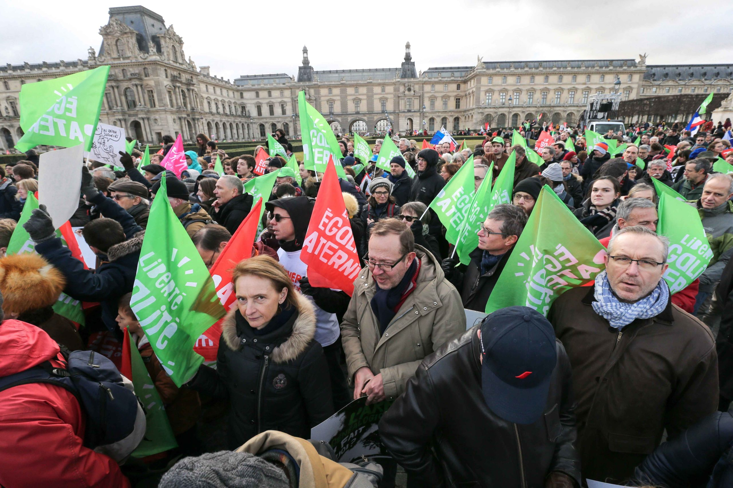 """Protesters hold flags in front of the Louvre Museum during a demonstration called by the movement 'La Manif pour tous' against the """"Medically-assisted procreation (MAP) without a father"""" in Paris on January 19, 2020, two days before the debate on the Bioet"""
