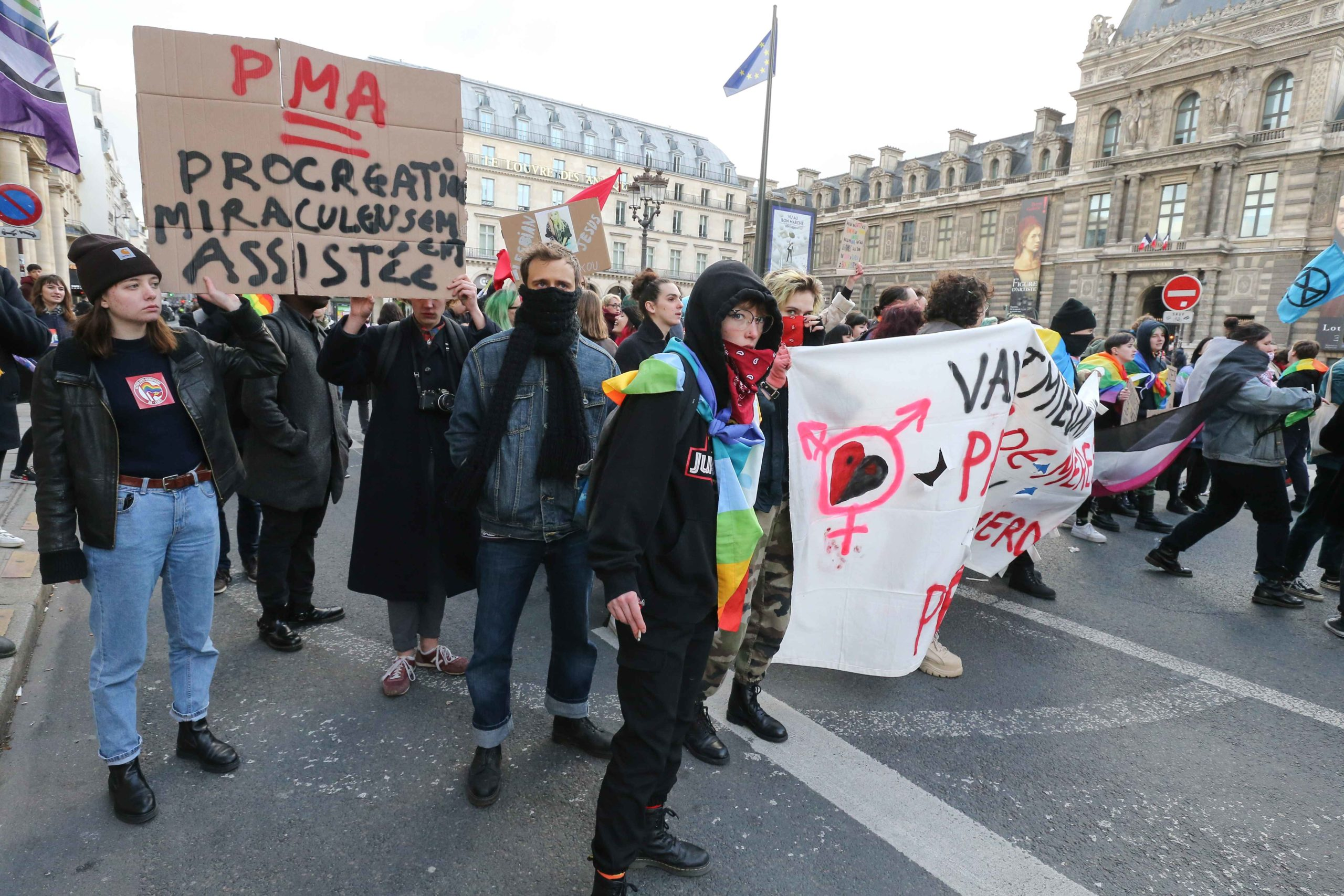 "Counter-demonstrators gather behin a banner during a demonstration called by the movement 'La Manif pour tous' against the ""Medically-assisted procreation (MAP) without a father"" in Paris on January 19, 2020, two days before the debate on the Bioethics Bil"