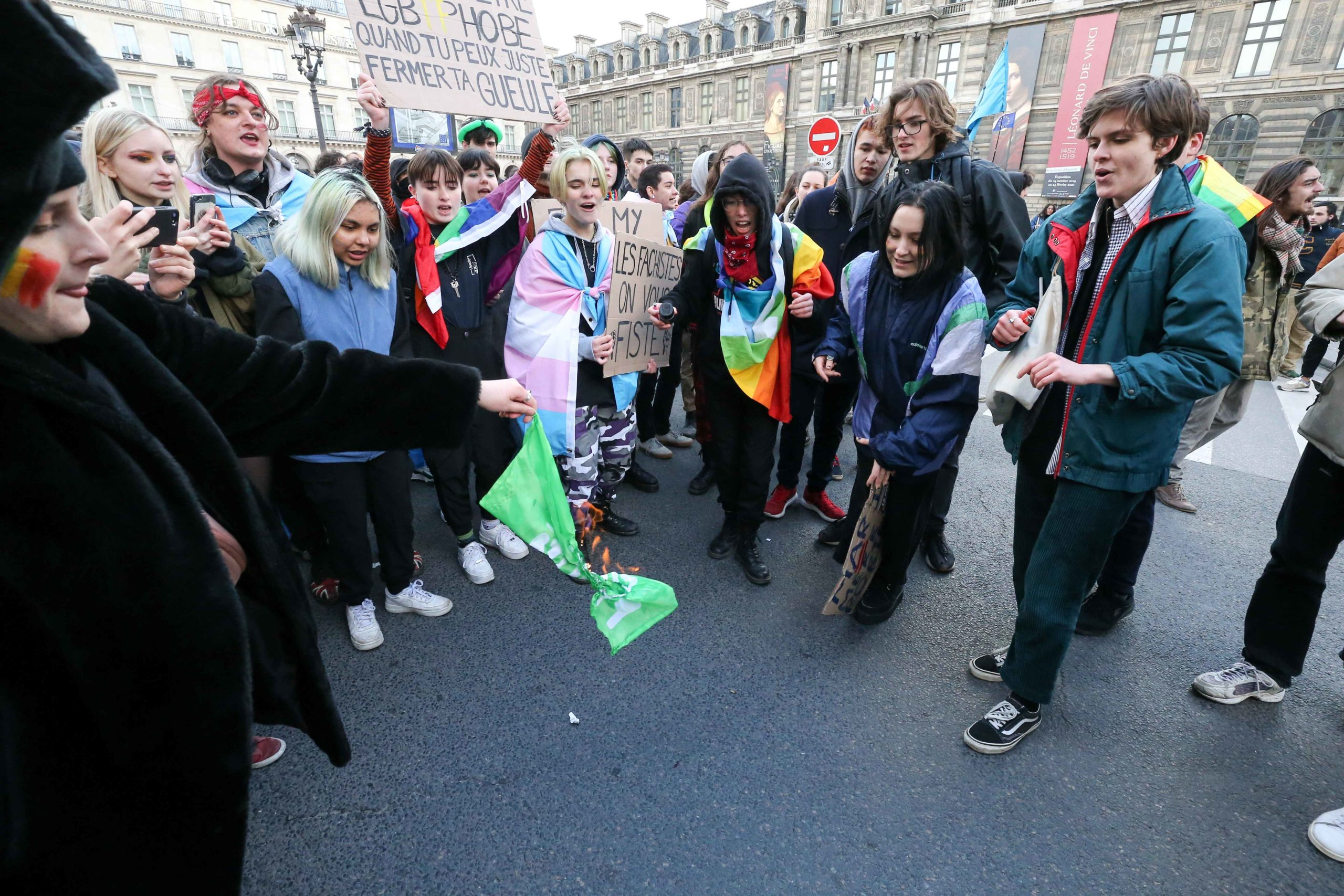 """Counter-demonstrators burn a flag of the movement 'La Manif pour tous' as protesters of this movement take part in a demonstration against the """"Medically-assisted procreation (MAP) without a father"""" in Paris on January 19, 2020, two days before the debate"""