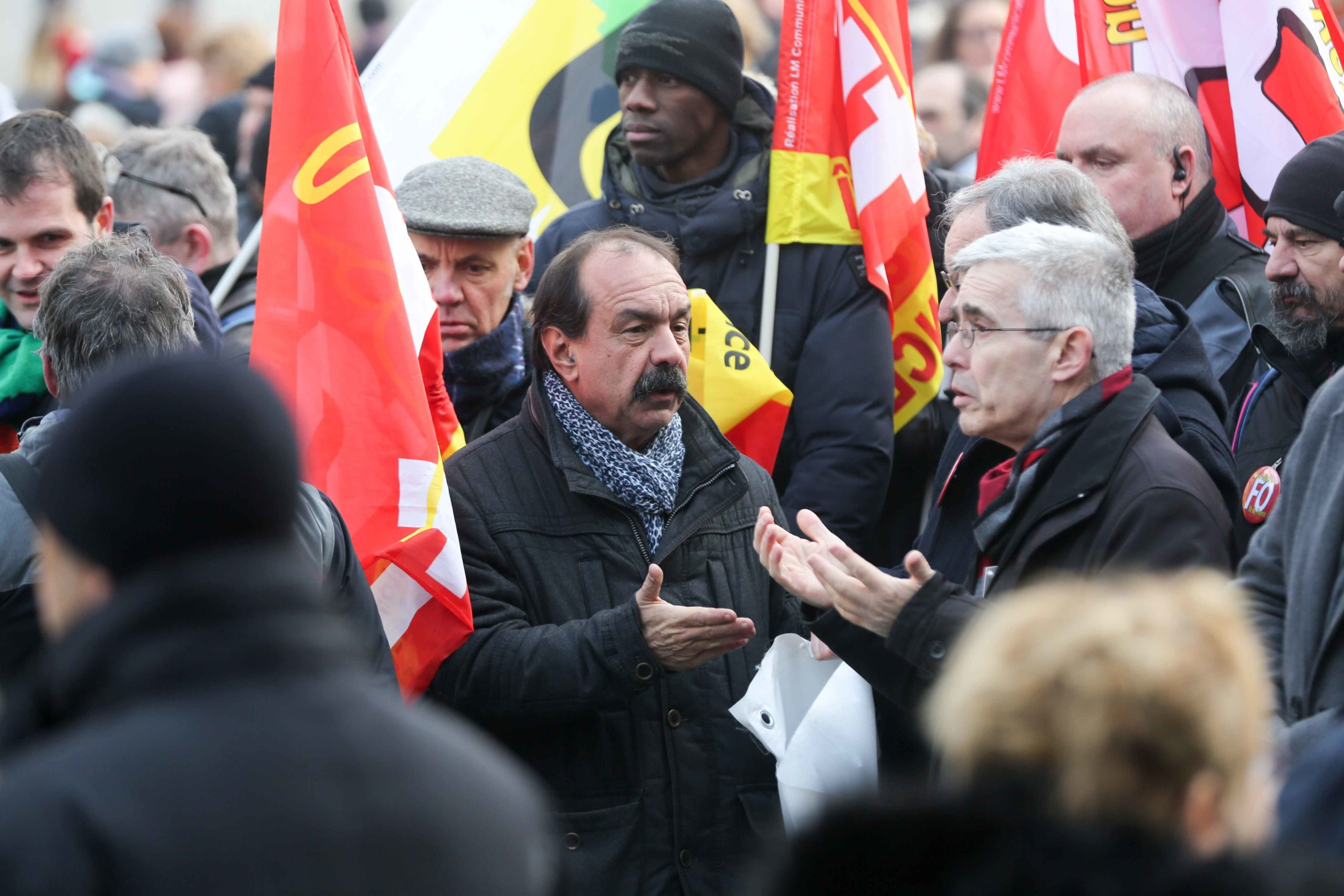 CGT union leader Philippe Martinez (C) speaks with the General secretary of French Union Force Ouvriere (FO) Yves Veyrier (R) during a demonstration in Paris on January 24, 2020 against the government pensions reform, which will be officially unveiled afte