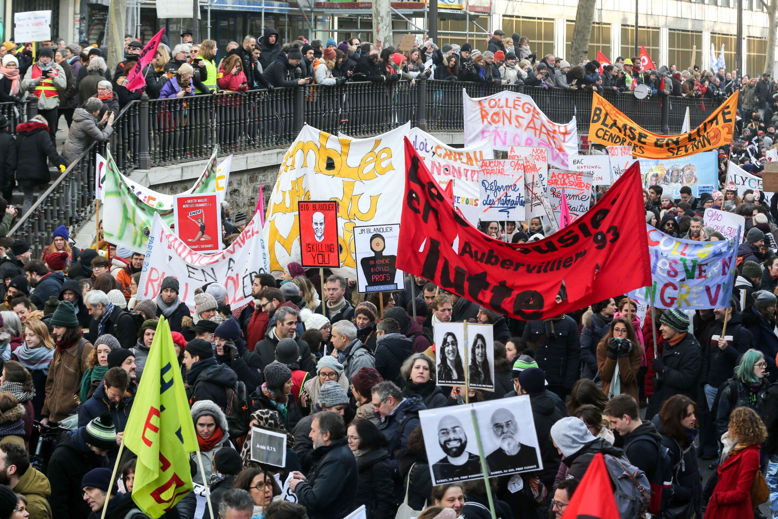 Protesters march in a street of Paris on January 24, 2020 during a demonstration against the government pensions reform, which will be officially unveiled after weeks of strikes by unions warning that millions of people will have to work longer. It will be