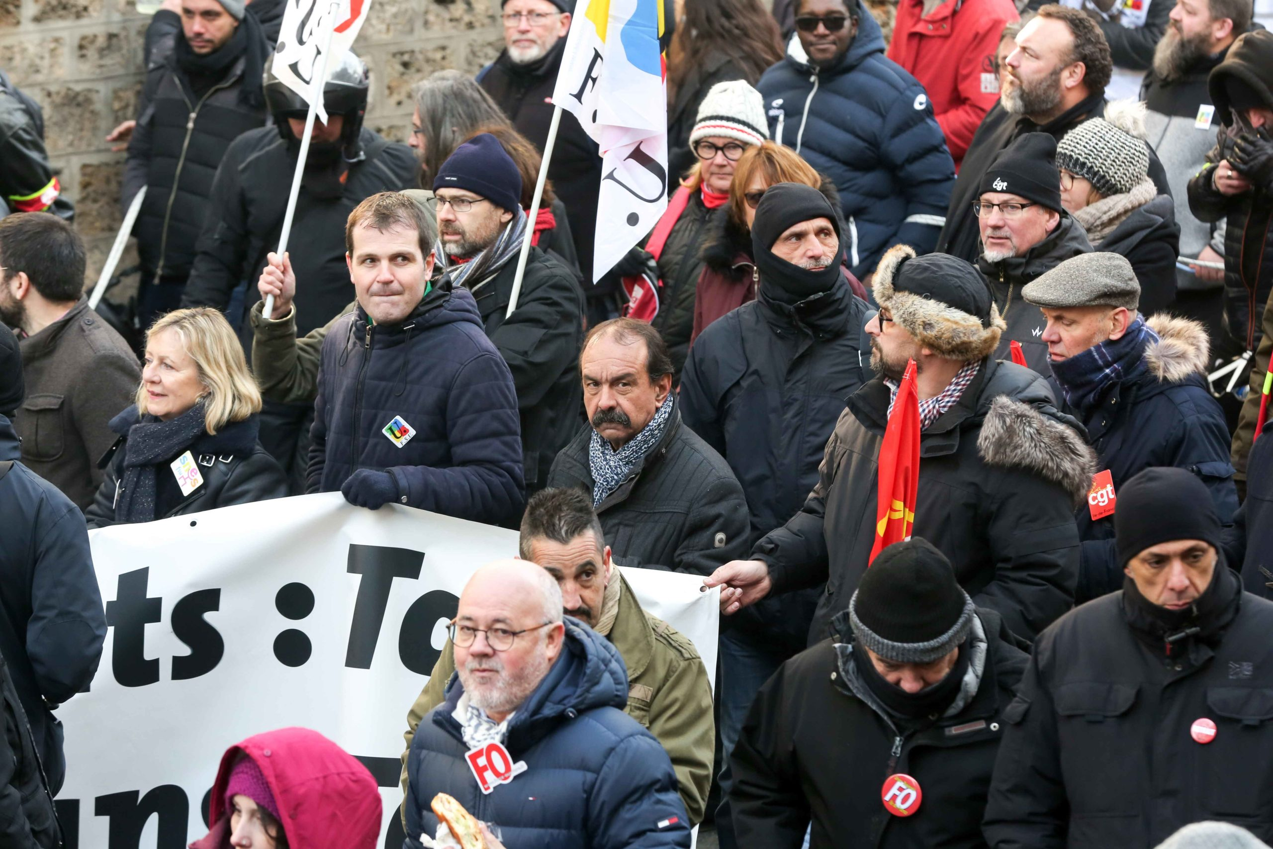 CGT union leader Philippe Martinez (C) takes part in a demonstration in Paris on January 24, 2020 against the government pensions reform, which will be officially unveiled after weeks of strikes by unions warning that millions of people will have to work l