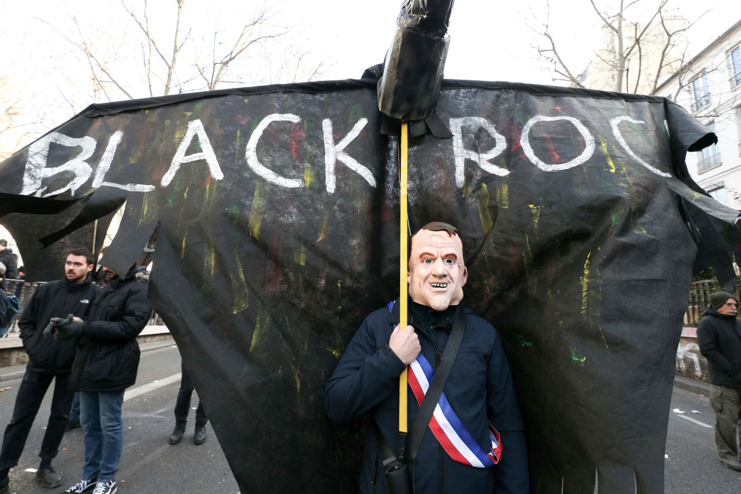 A protestor wearing the mask of the French President Emmanuel Macron holds up a puppet reading, 'Black rock » during a demonstration in Paris on January 24, 2020 against the government pensions reform, which will be officially unveiled after weeks of stri