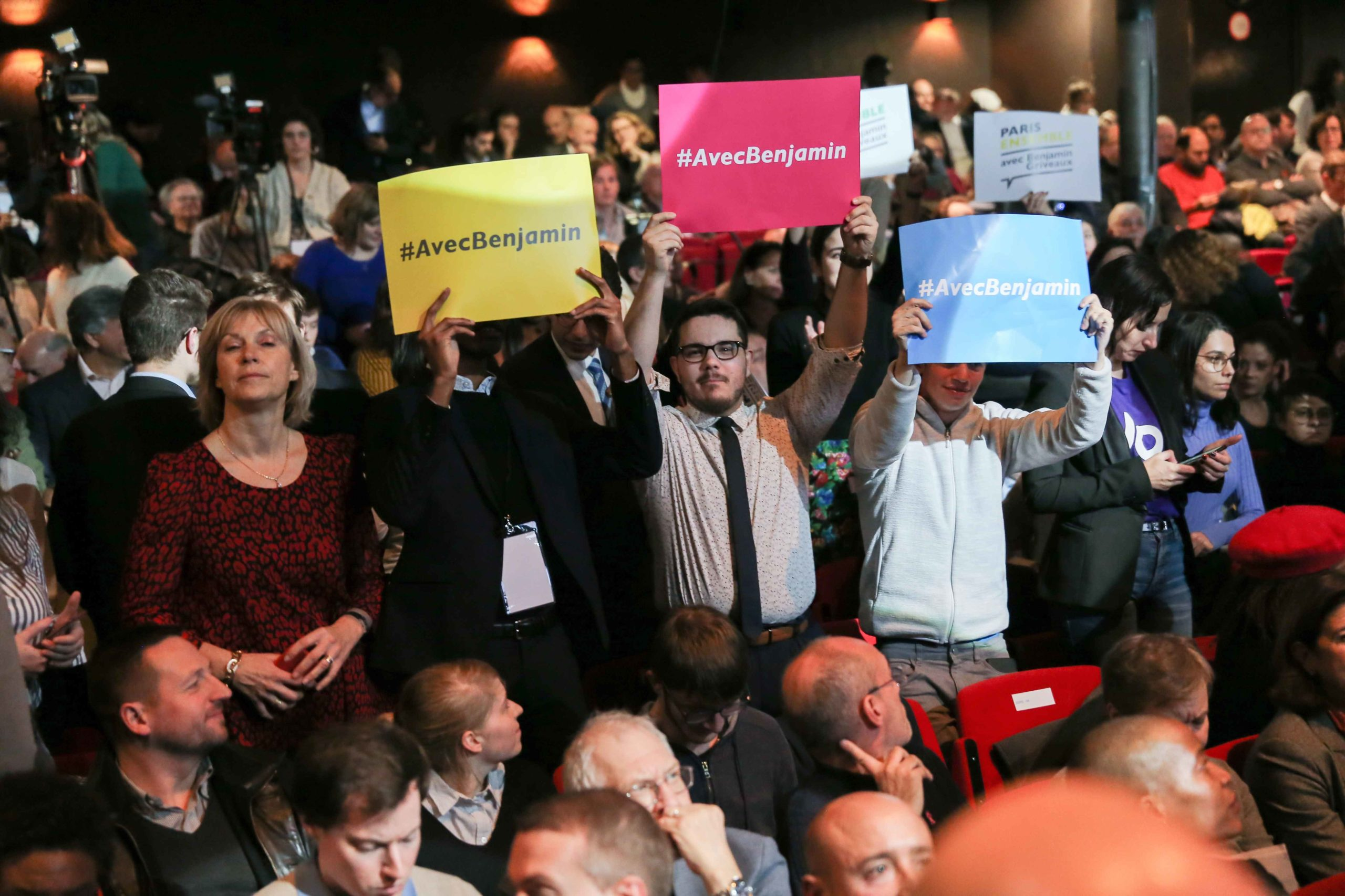 Supporters turn up holdings signs that say « With Benjamin » during the Benjamin Griveaux meeting, at the Bobino theater in Paris, on January 27, 2020. Benjamin Griveaux is the official La Republique en Marche (LREM) candidate for the Paris 2020 mayoral
