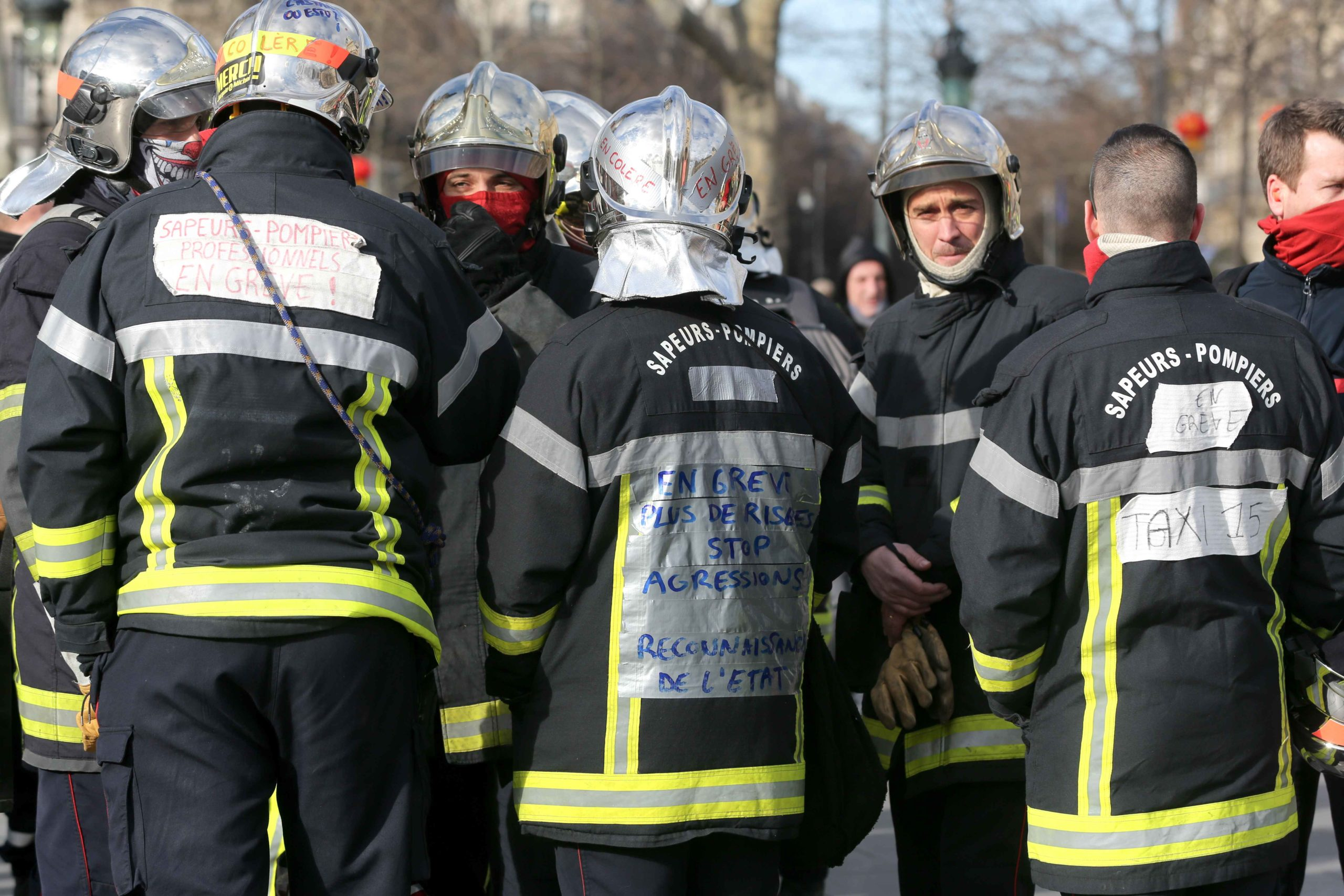 "A firefighter sporting a message on his uniform reading ""on strike"" takes part in a demonstration at Republic Square to protest against French government's plan to overhaul the country's retirement system in Paris, on January 28, 2020."