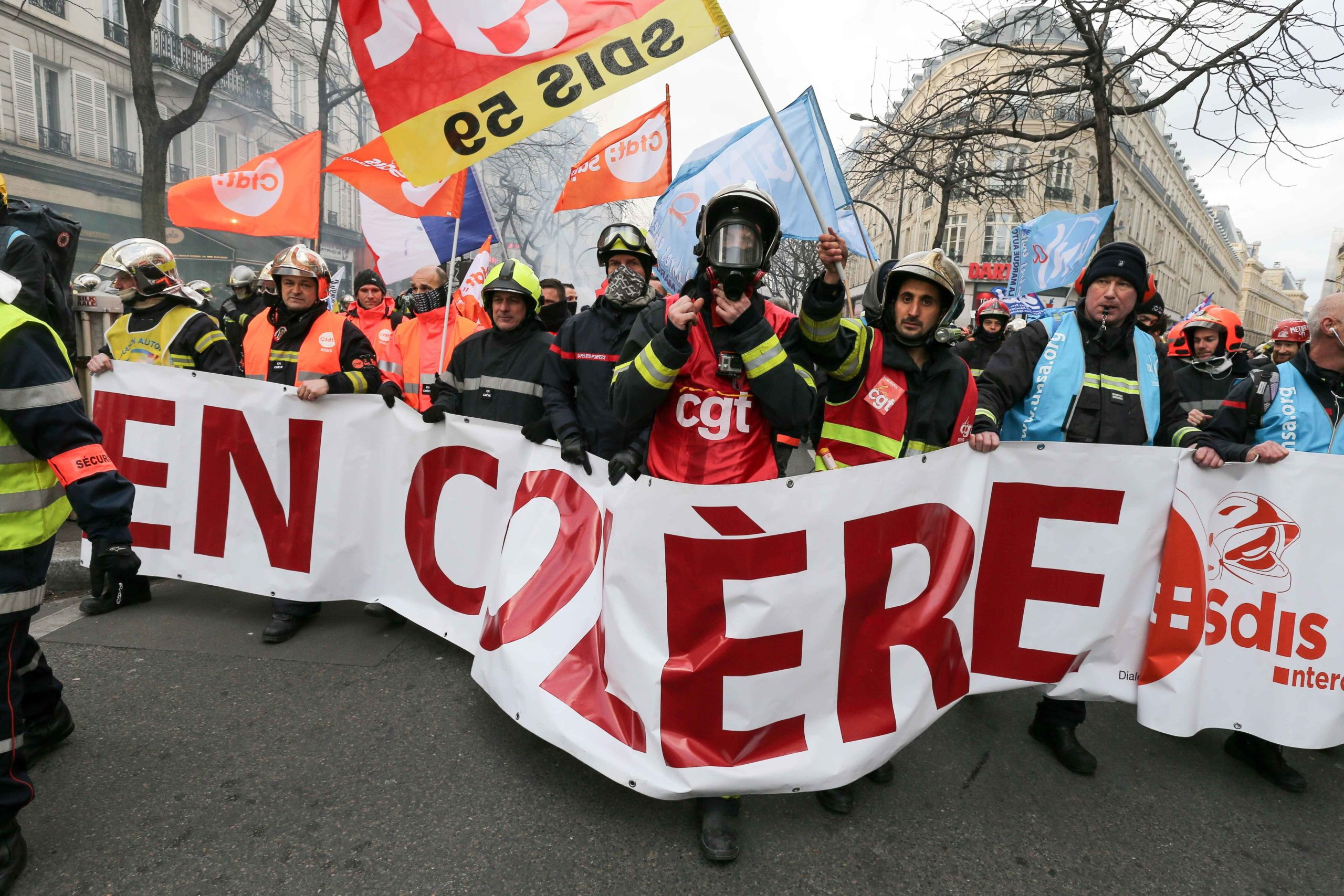 Firefighters march behind a banner reading « Angry firefighters » during a demonstration to protest against French government's plan to overhaul the country's retirement system in Paris, on January 28, 2020.