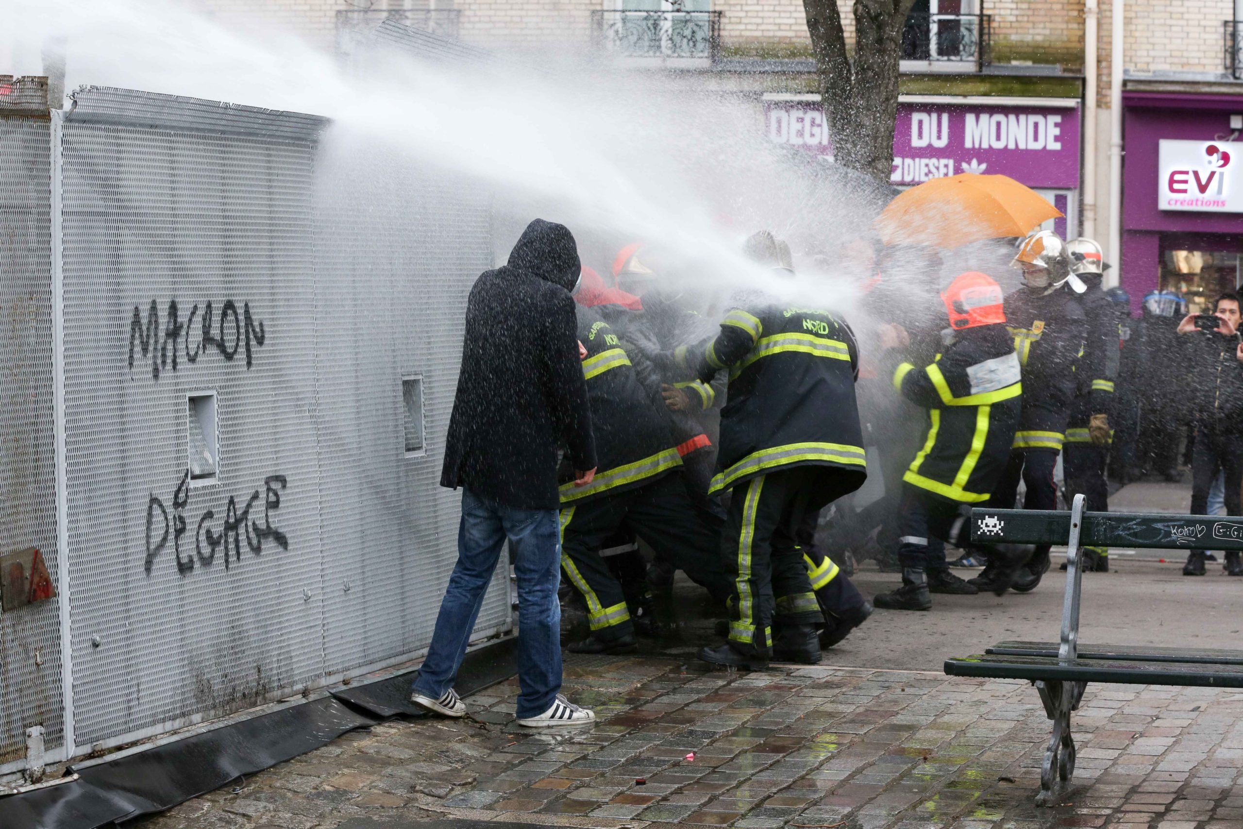 Firefighters try to open a path in a riot barricade and were repelled by water canons during a demonstration to protest against French government's plan to overhaul the country's retirement system in Paris, on January 28, 2020.