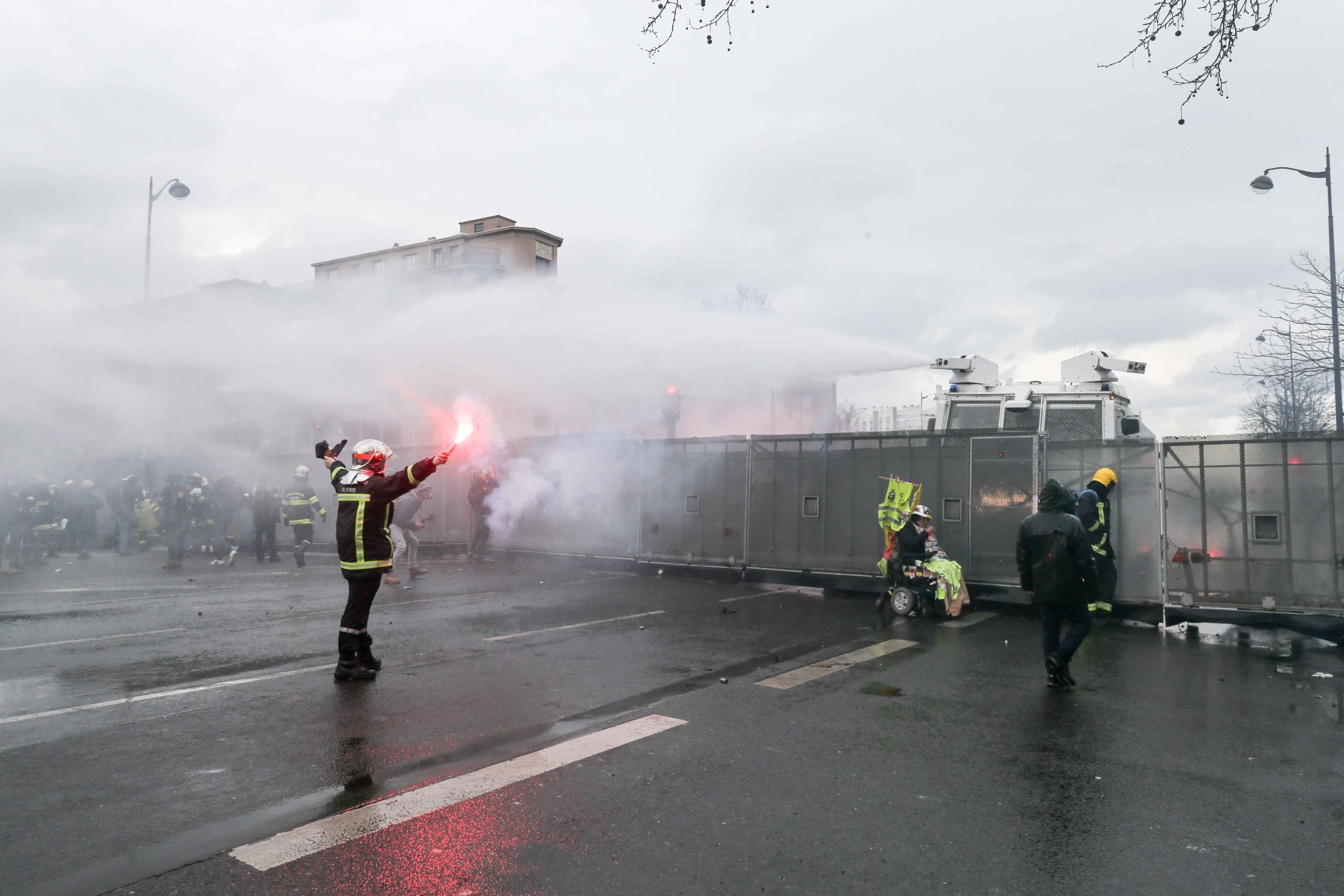 A firefighter stands in front of water canons during a demonstration to protest against French government's plan to overhaul the country's retirement system in Paris, on January 28, 2020.