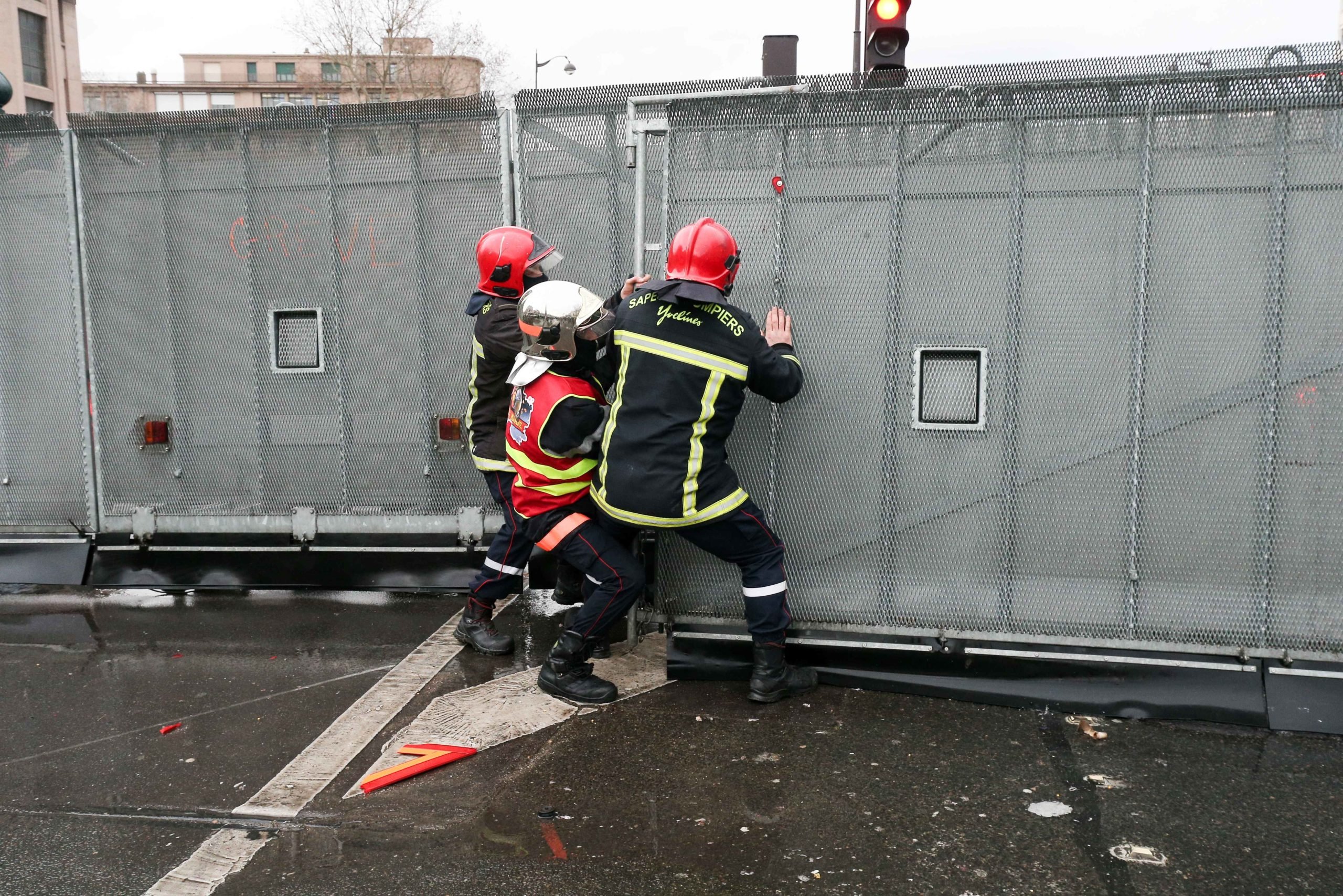 Three firefighters try to open a path in a riot barricade during a demonstration to protest against French government's plan to overhaul the country's retirement system in Paris, on January 28, 2020.