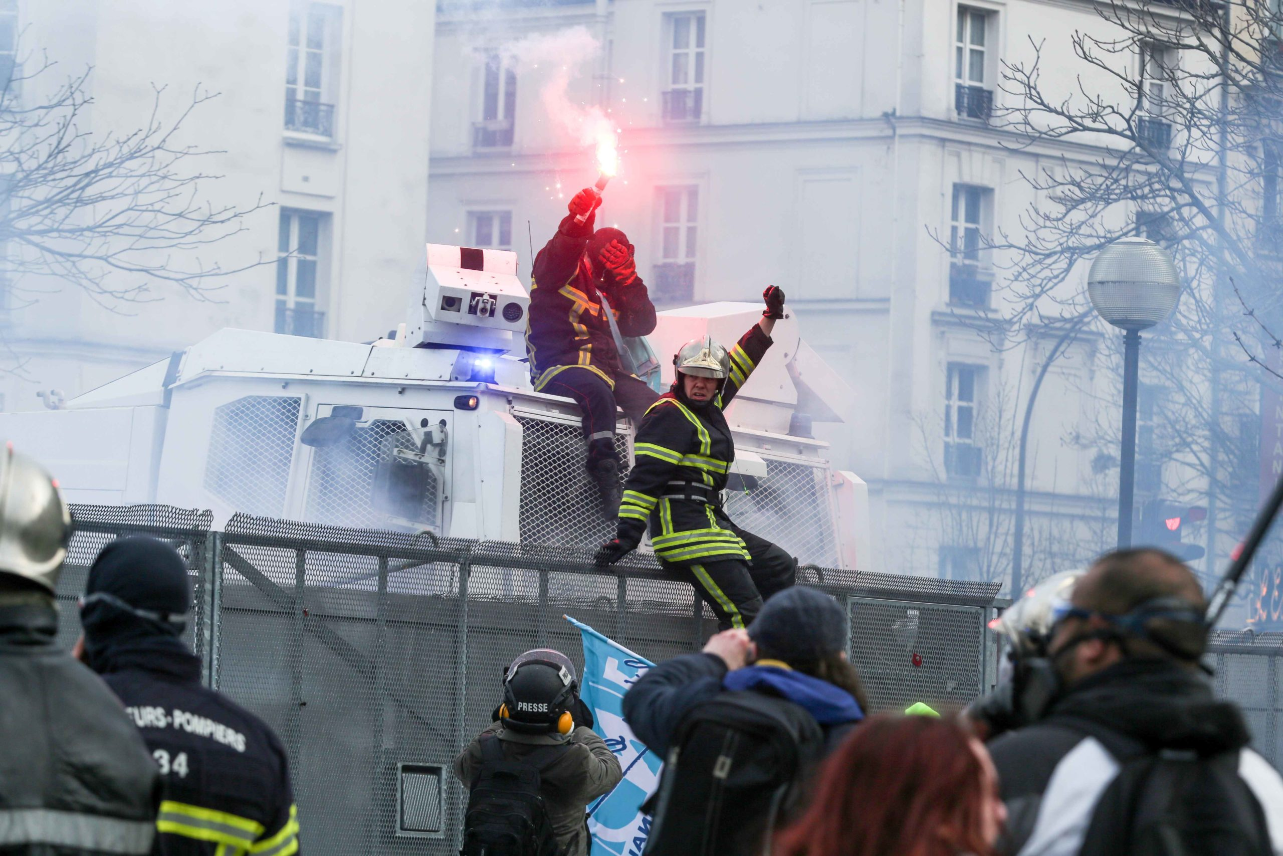 Two firefighters manage to ride a water canon during a demonstration to protest against French government's plan to overhaul the country's retirement system in Paris, on January 28, 2020.