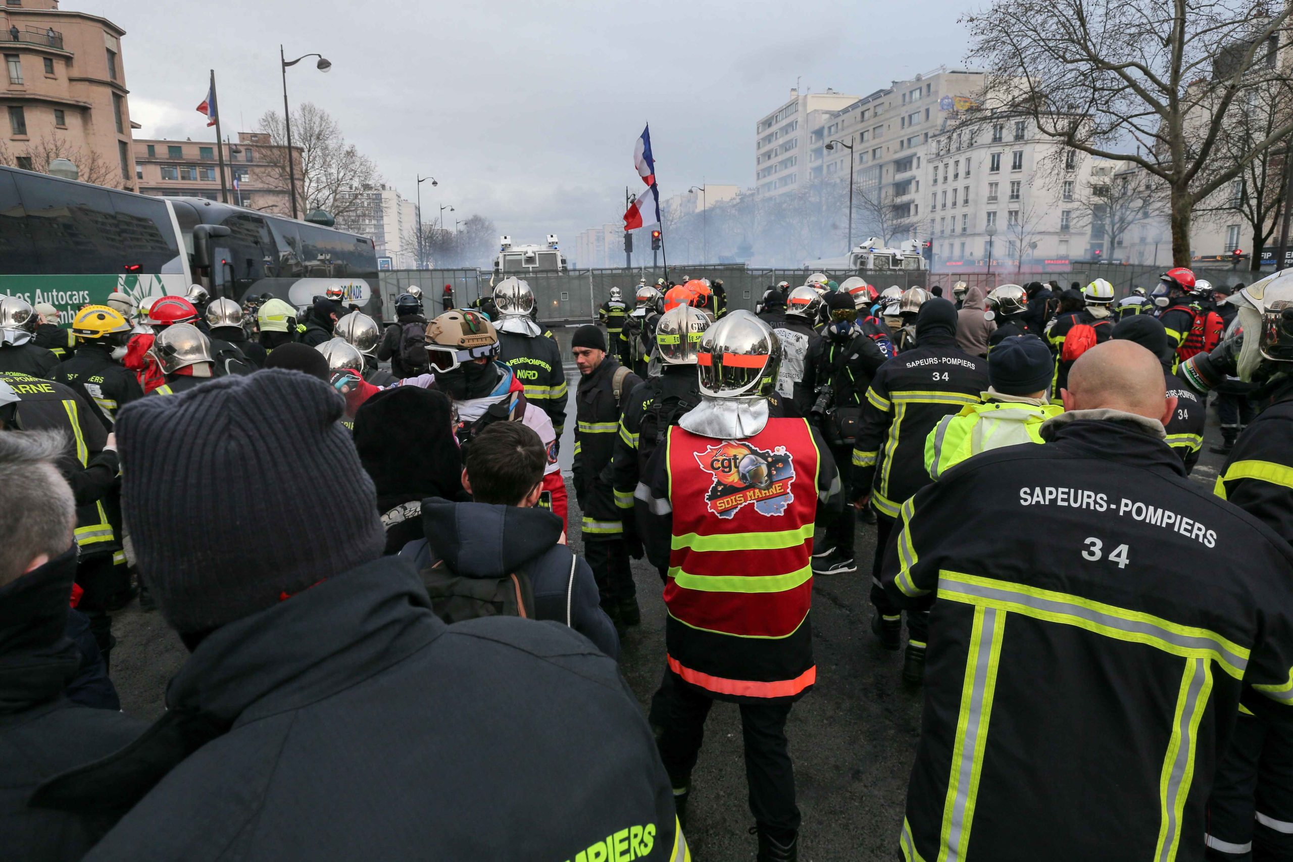FirefighterS stands in front of a riot barricade and water canons during a demonstration to protest against French government's plan to overhaul the country's retirement system in Paris, on January 28, 2020.