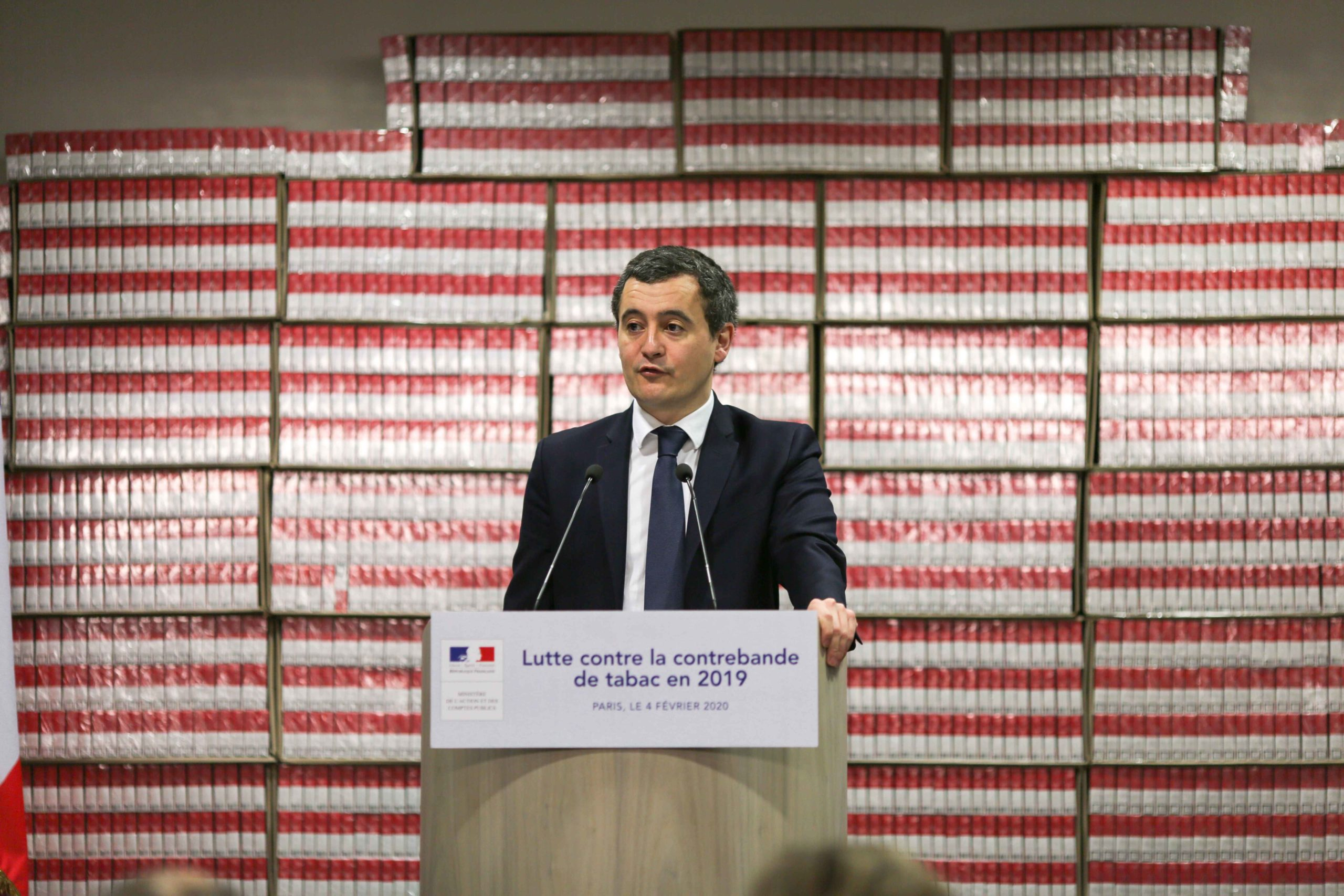 French Minister of Public Action and Accounts Gerald Darmanin (C) presents the 2019 results of the National plan to mobilise customs against the trafficking of tobacco and cigarettes at the Paris regional customs service on February 04, 2020, in front of c